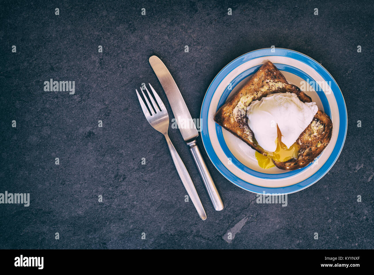 Poached egg on toast on a slate background from above. Vintage filter applied Stock Photo