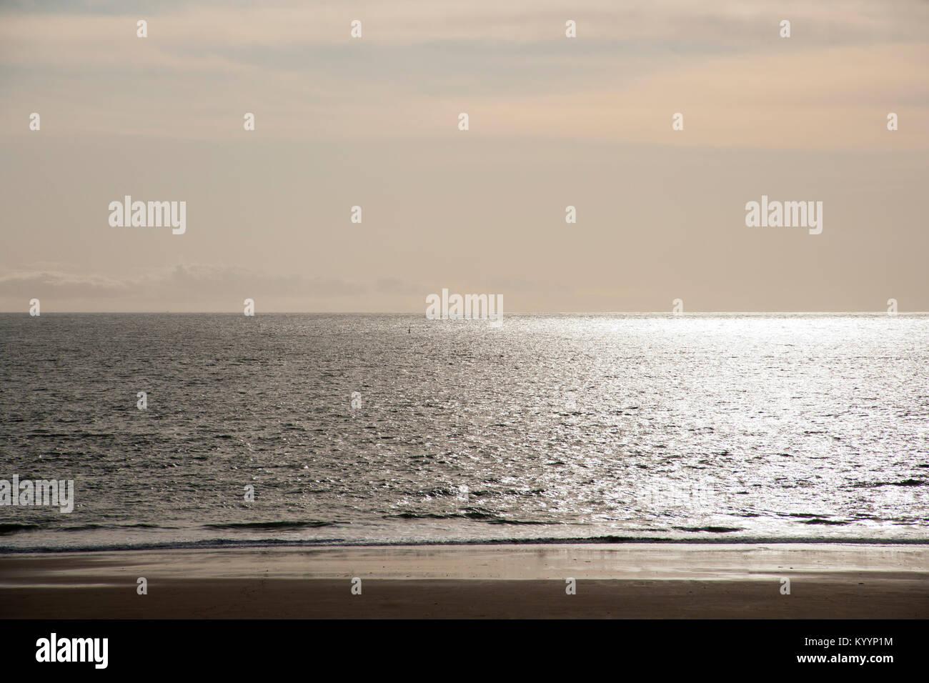 Sunlight gleaming on atmospheric peaceful empty beach and sea horizon - Stock Image