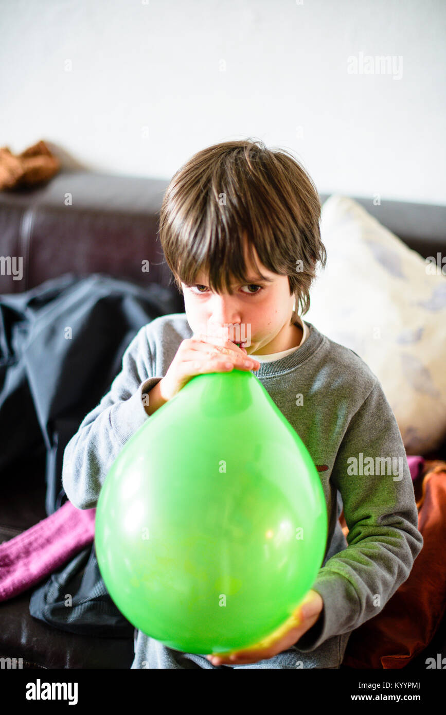 child inflates green balloon for birthday party in his home - Stock Image