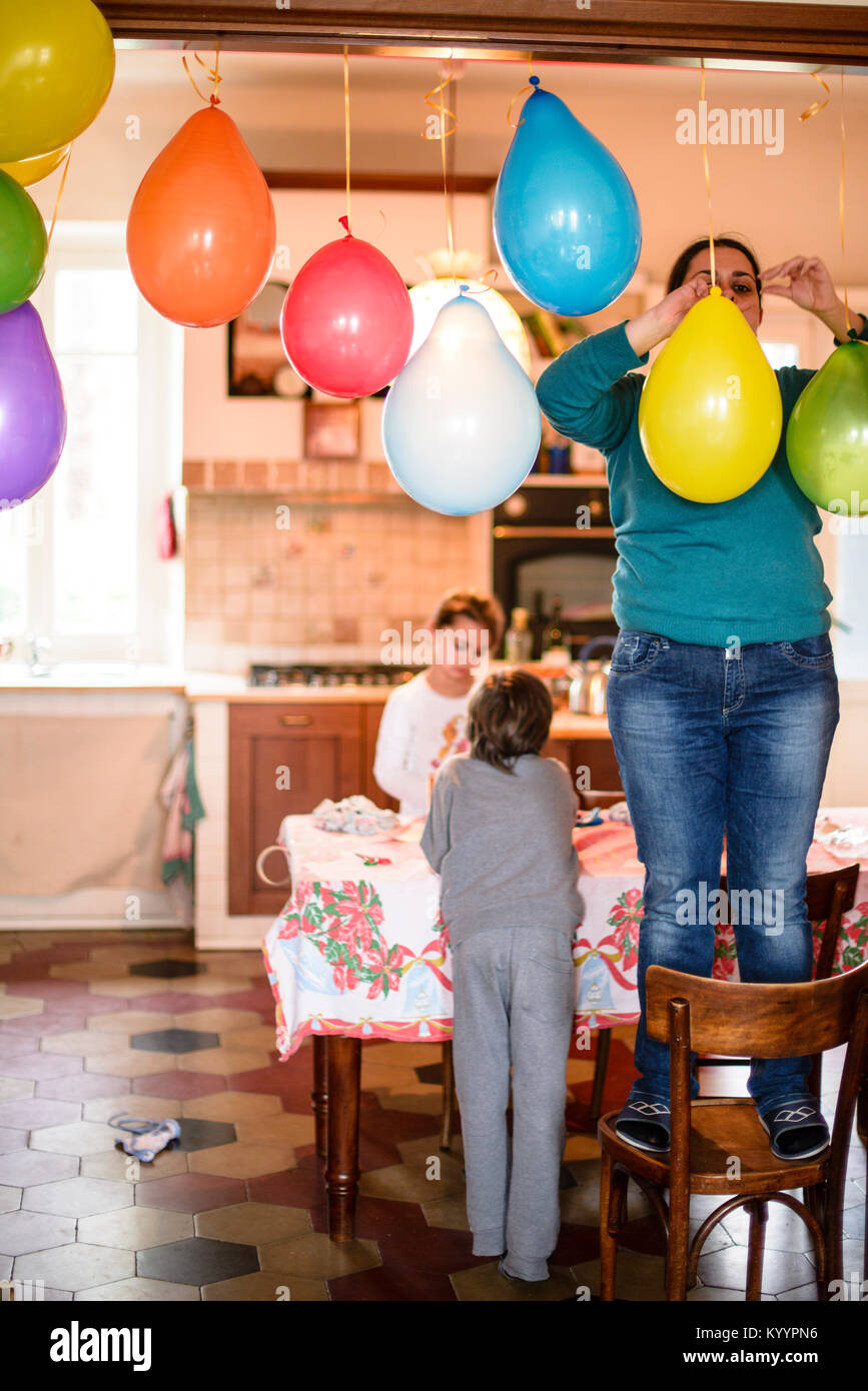 Mother With Children Hang Colorful Balloons For Birthday Party In Her Home Standing On The Chair Hangs At Door