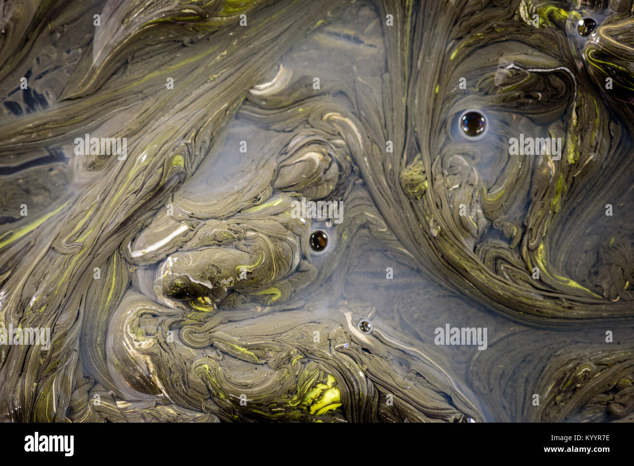 Congealed oil on water in yellow and black creating an abstract organic pollution based design. Copy space area Stock Photo