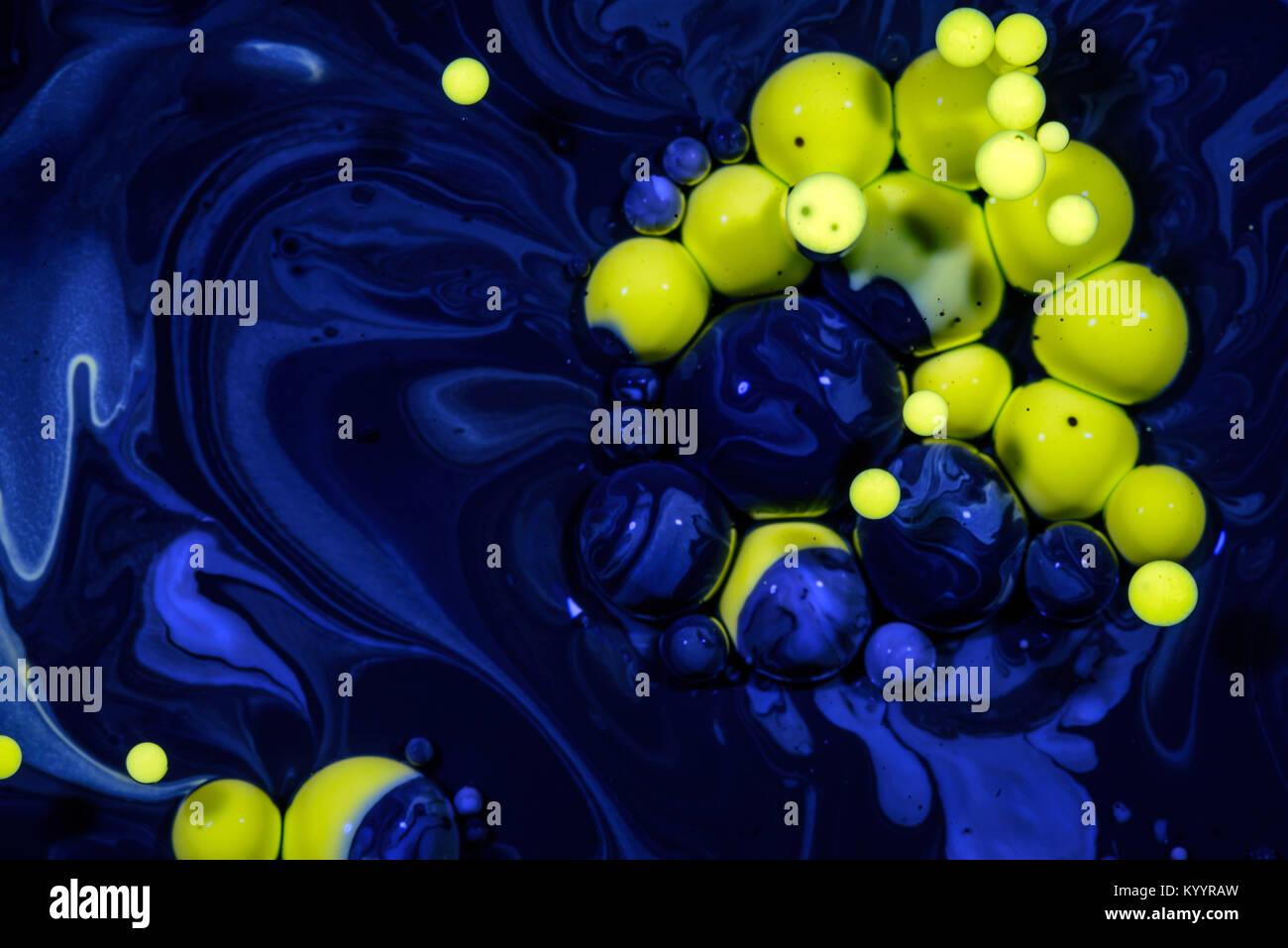 Yellow drops of oil suspended in blue chemical oil slick creating an abstract between nature and a polluted hazardous Stock Photo