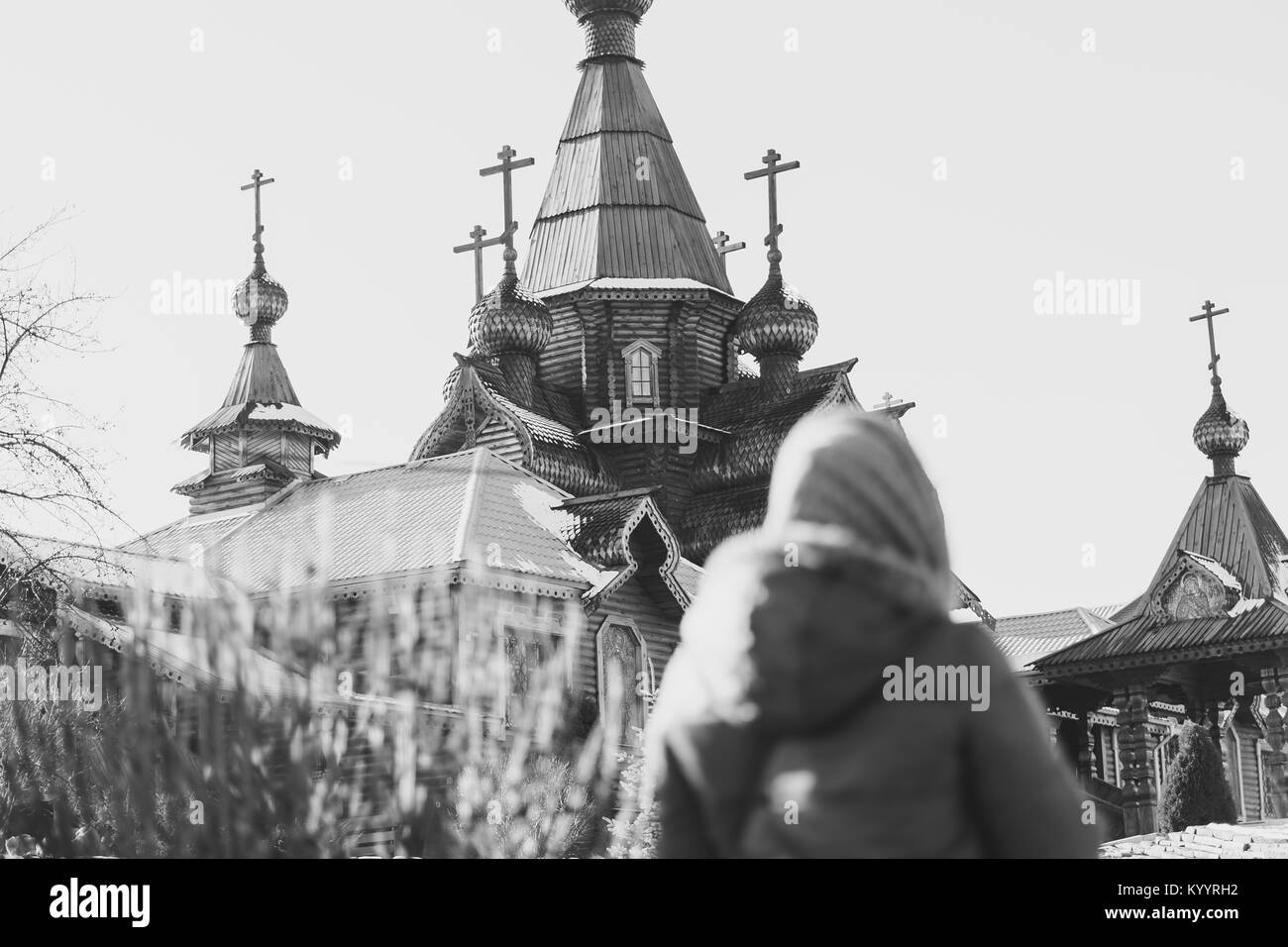 a woman looks at a wooden Church in Russia - Stock Image