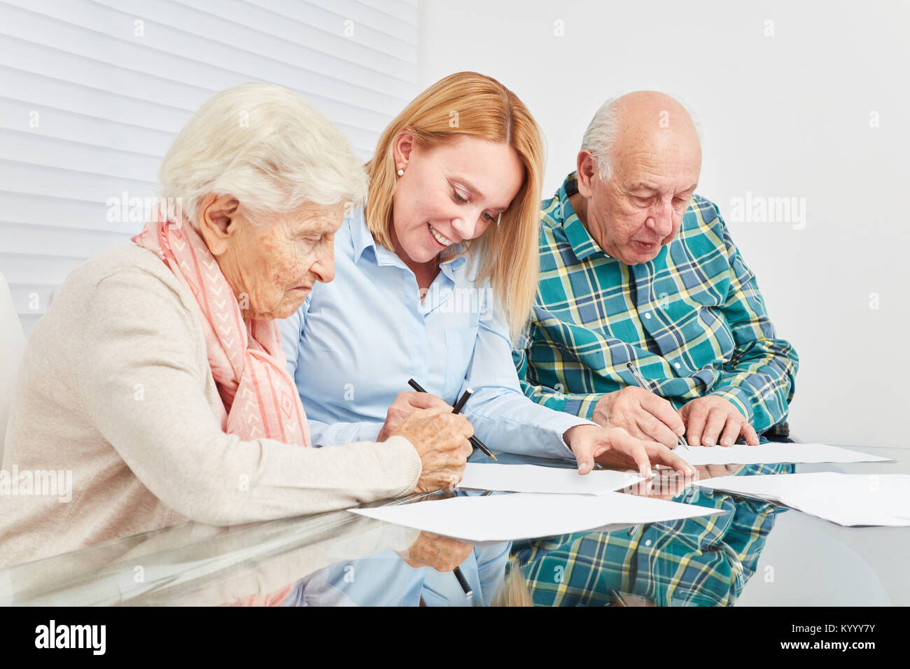 Woman advises senior couple on tax and finance with home documents - Stock Image