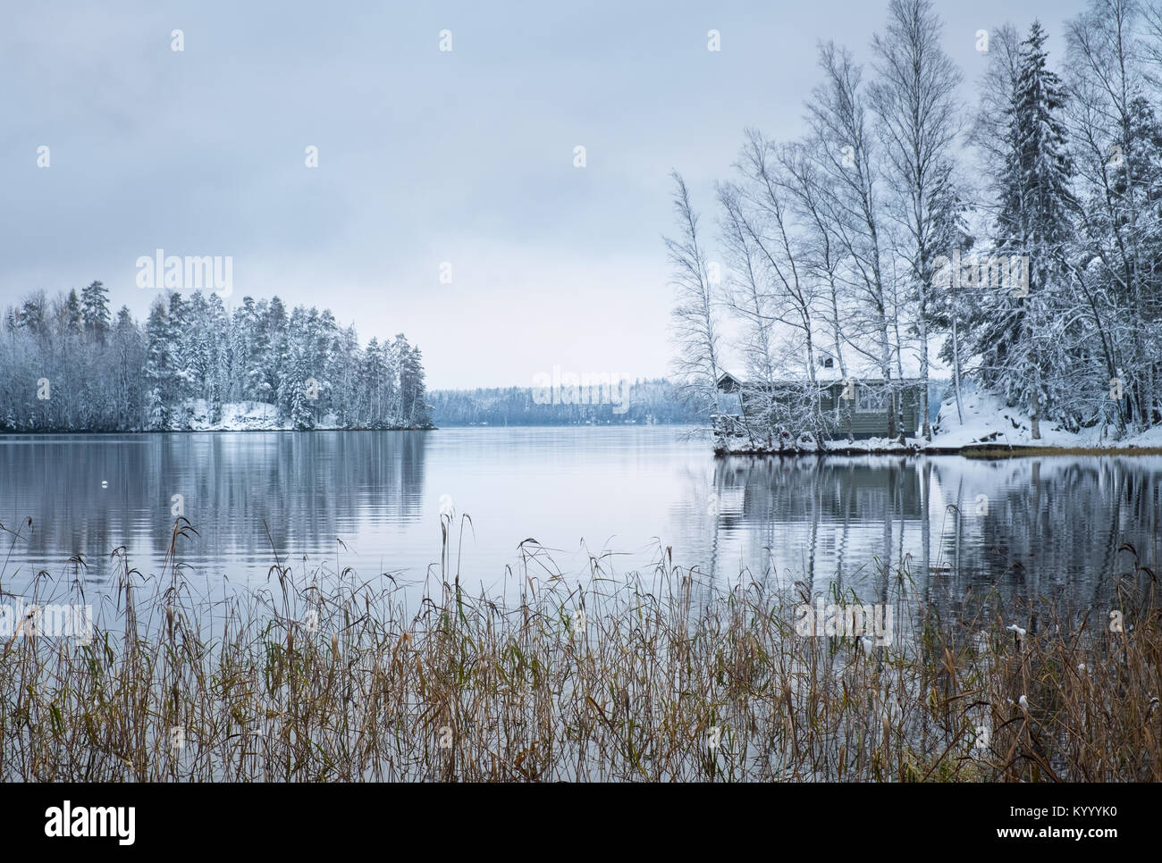 Winter landscape with sauna cottage and peaceful lake at evening in Finland - Stock Image