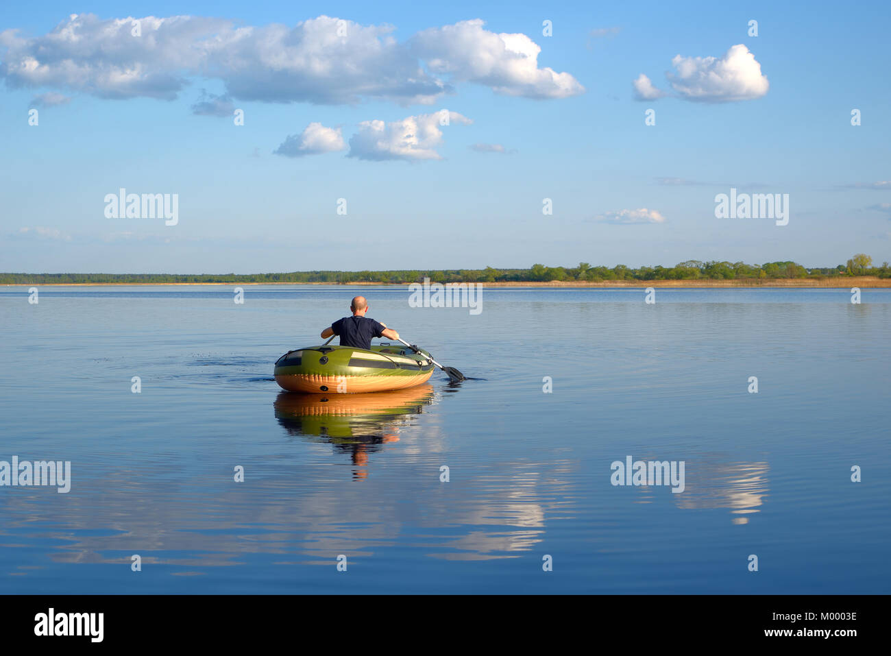 Man in an inflatable boat floats on the river, the view from the back Stock Photo
