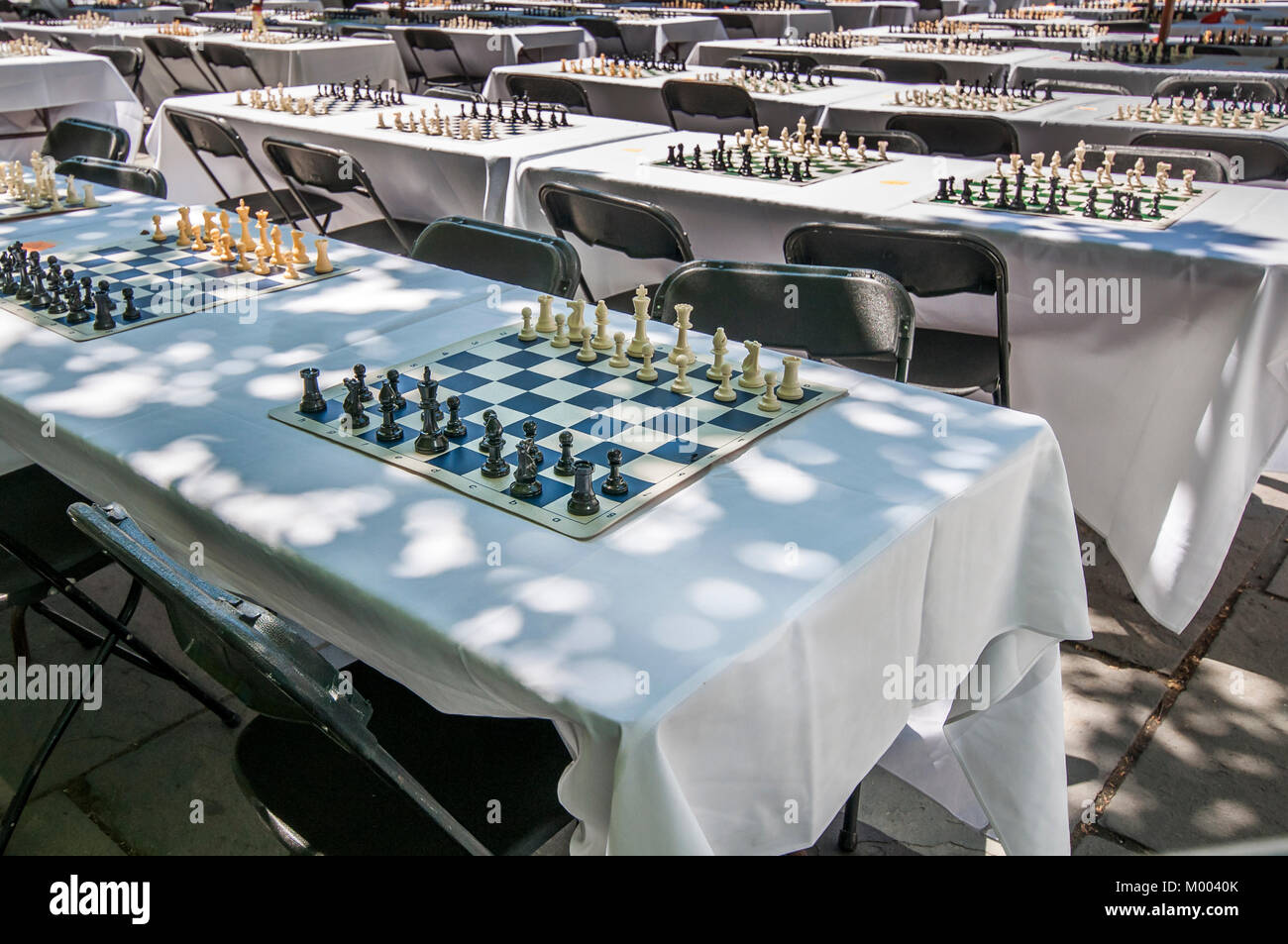 Numerous chessboards with black and white chess pieces are set up on tables with white linen cloths ready for an - Stock Image