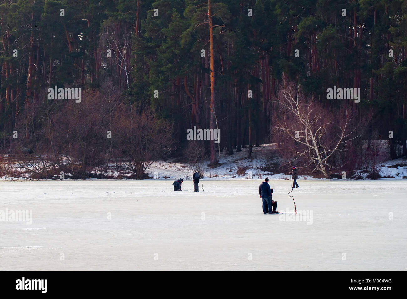 Winter fishing. River, lake near forest in ice. Anglers, Fishermens during your favorite leisure time. - Stock Image