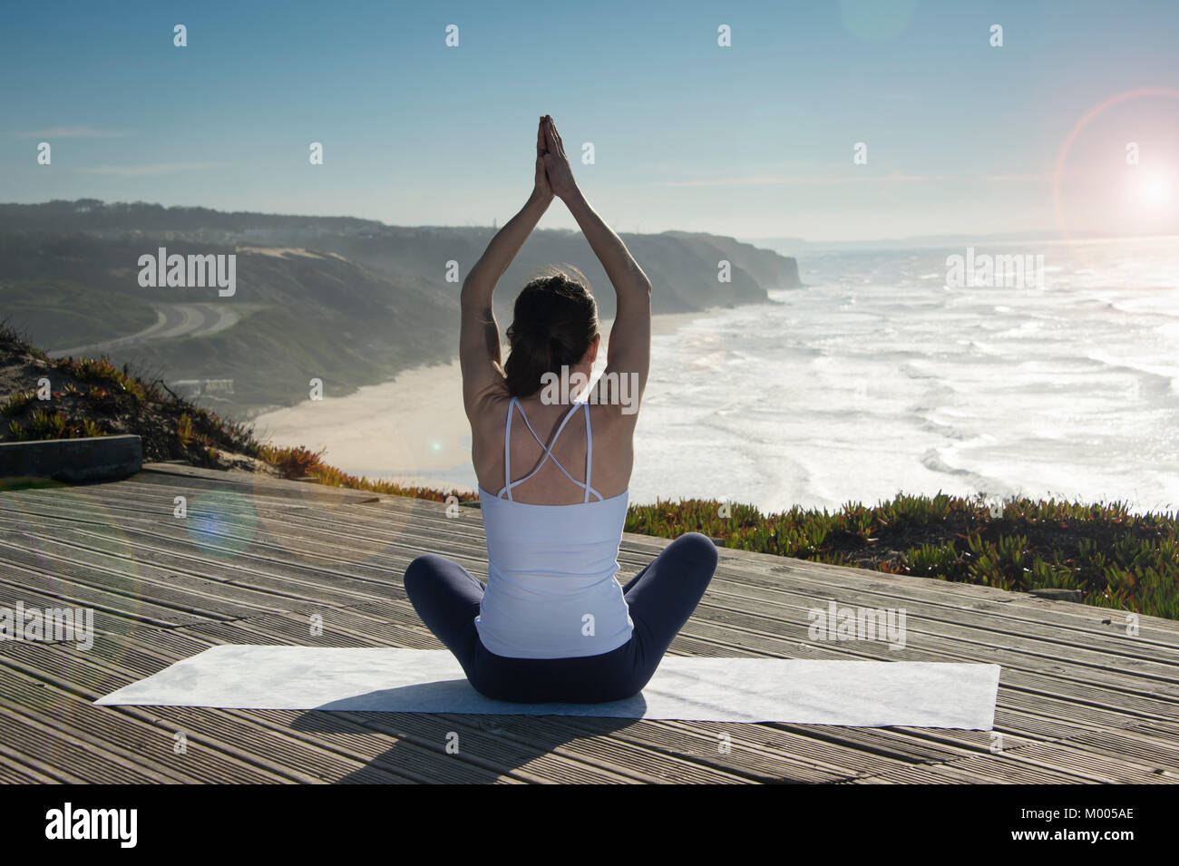 woman sitting in the lotus position meditating with a view over the sea and cliffs. Back view. - Stock Image