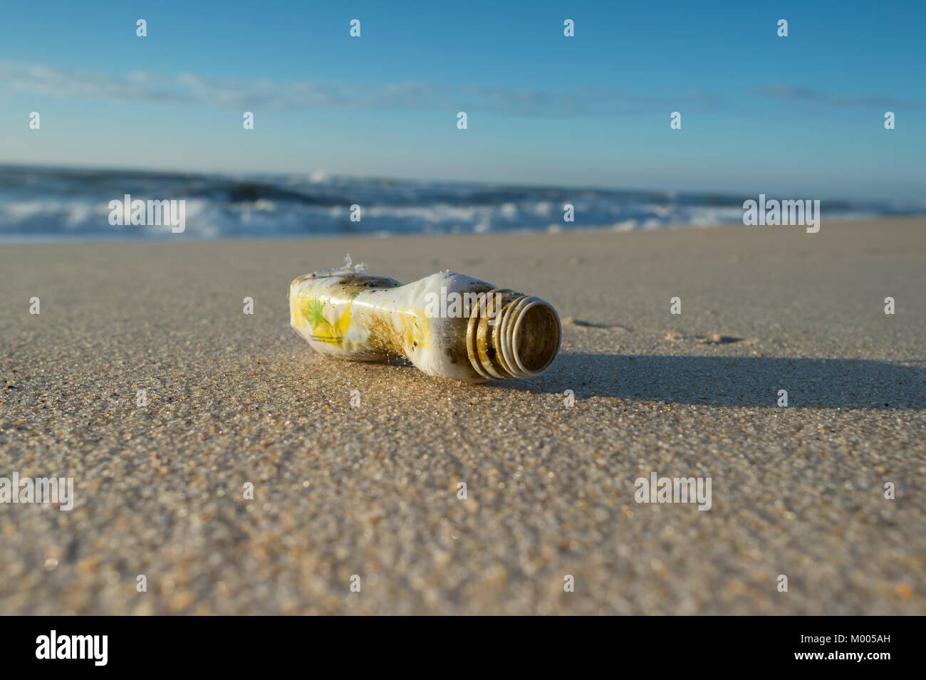 plastic bottle washed up on a deserted beach, Ocean pollution with non-recyclable plastic. - Stock Image