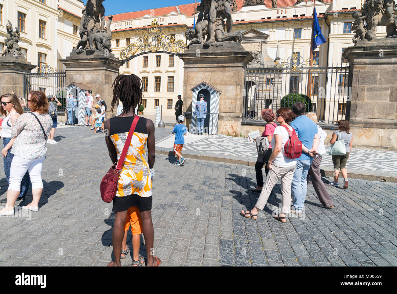 PRAGUE - AUGUST 29: Black woman with dreadlock hair stands  while other tourists walk around looking at Prague Castle - Stock Image