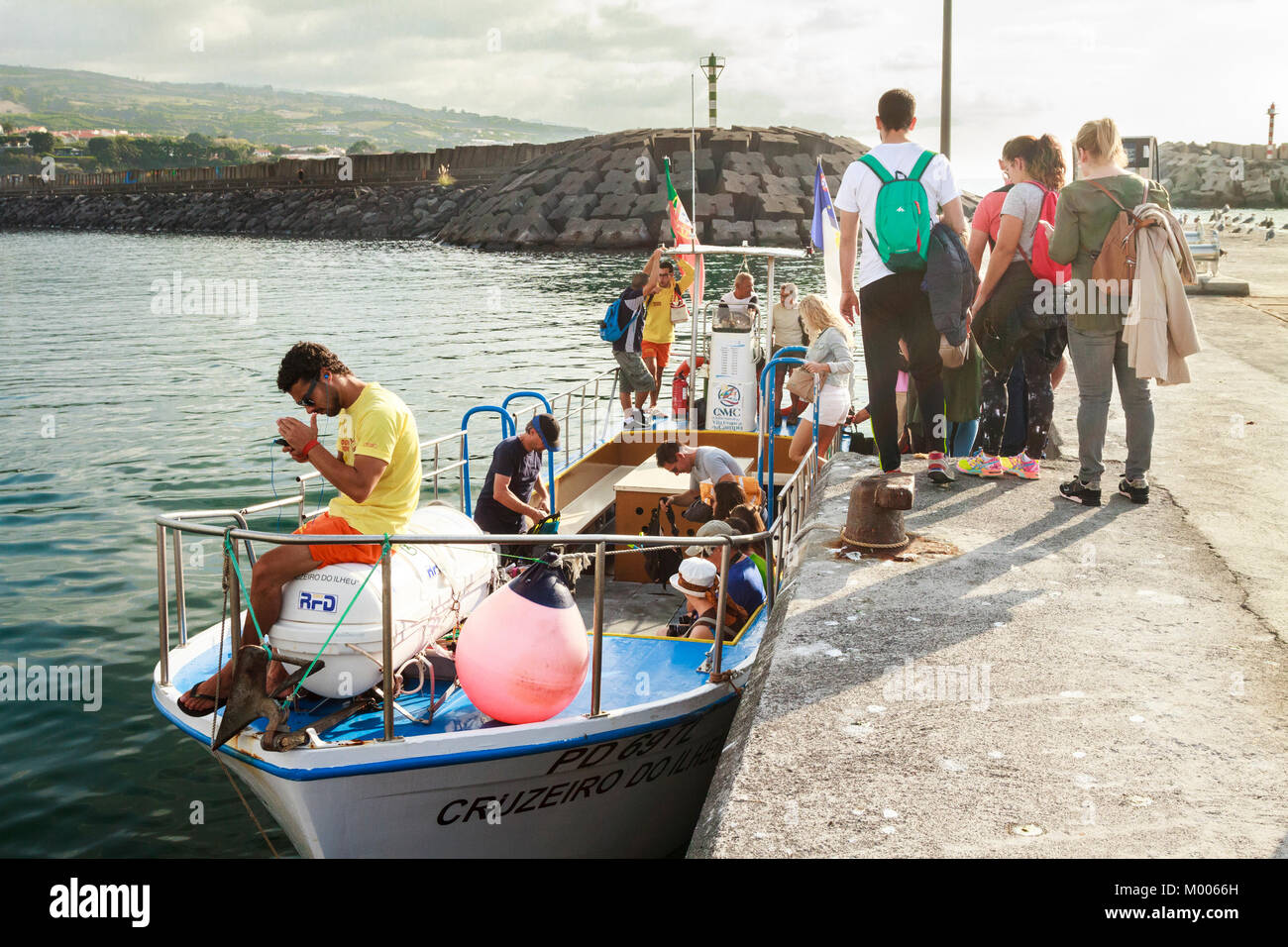 Tourists boarding a boat to travel to islet of Vila franca do Campo from Sao Miguel, Azores, Portugal - Stock Image