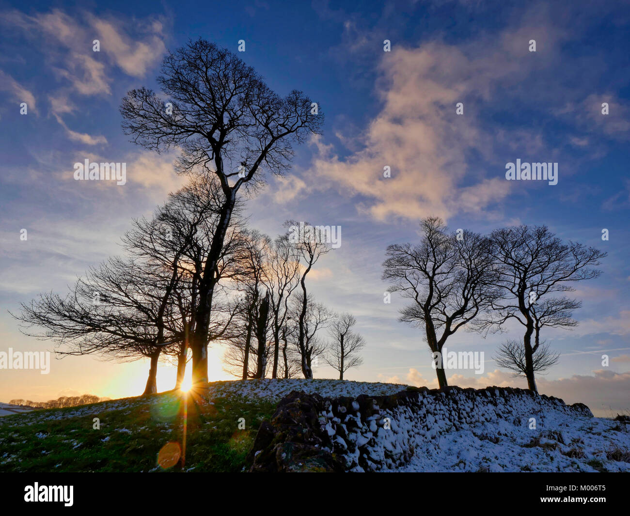 Moat Low Derbyshire spectacular sunset over the snow capped Bronze Age Round Barrow near Tissington in the Peak - Stock Image