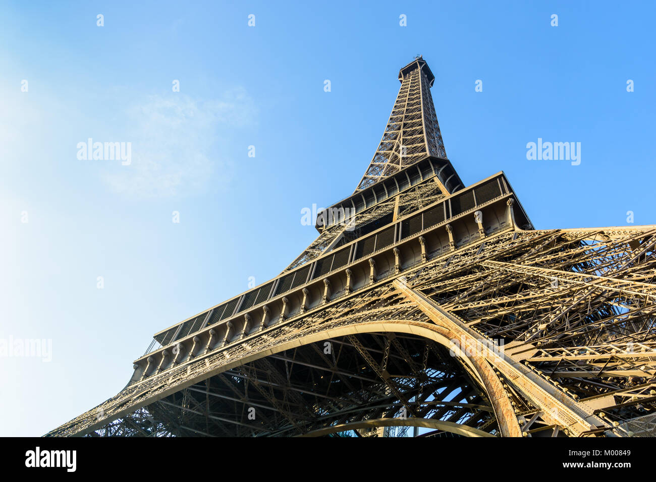 Dynamic view from below of the Eiffel Tower against blue sky. - Stock Image