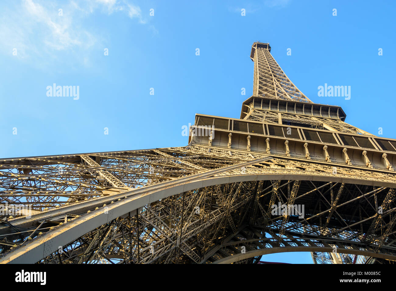 Dynamic low angle view of the Eiffel Tower against blue sky. - Stock Image