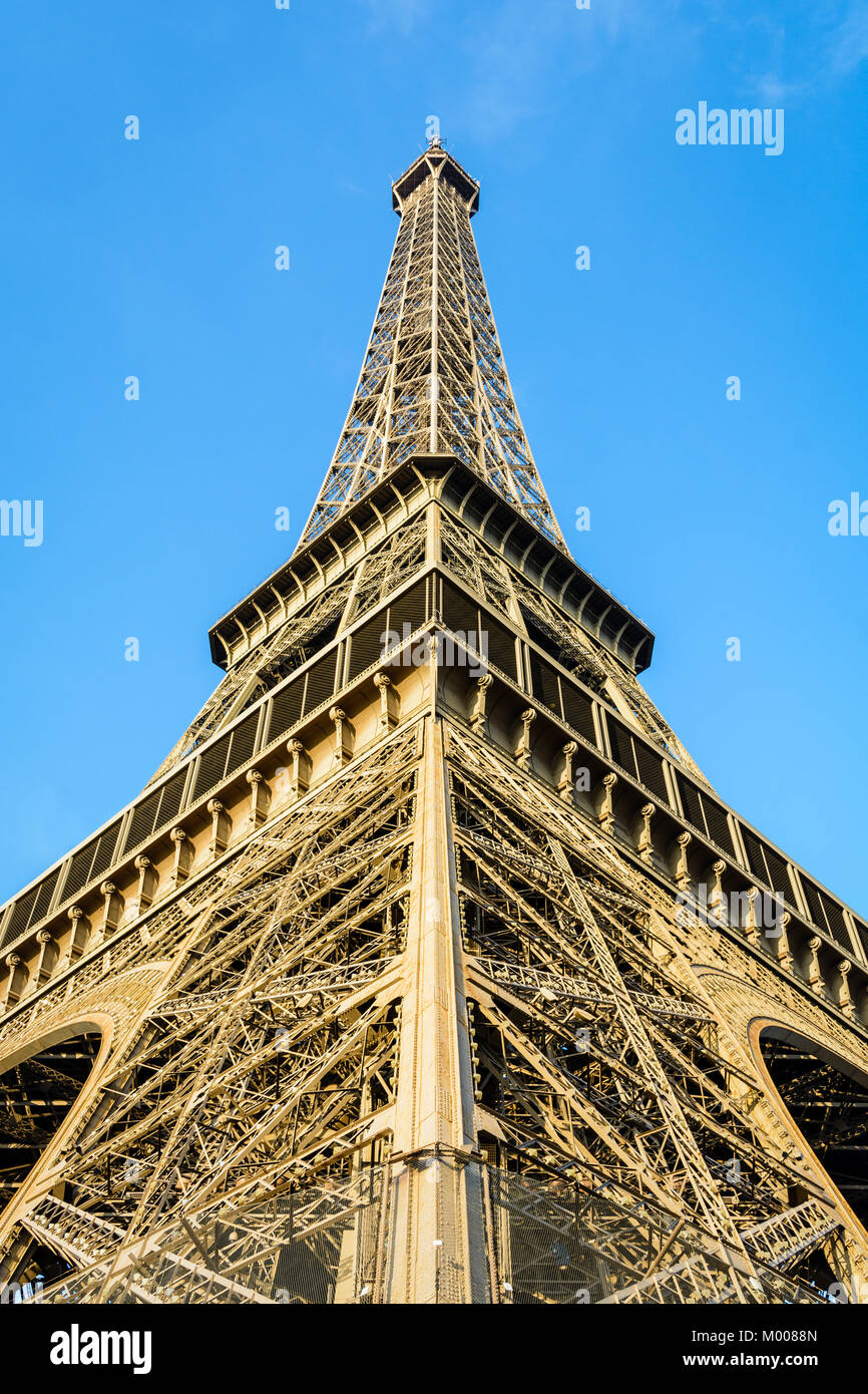 Symmetrical low angle view of the Eiffel Tower against blue sky. - Stock Image