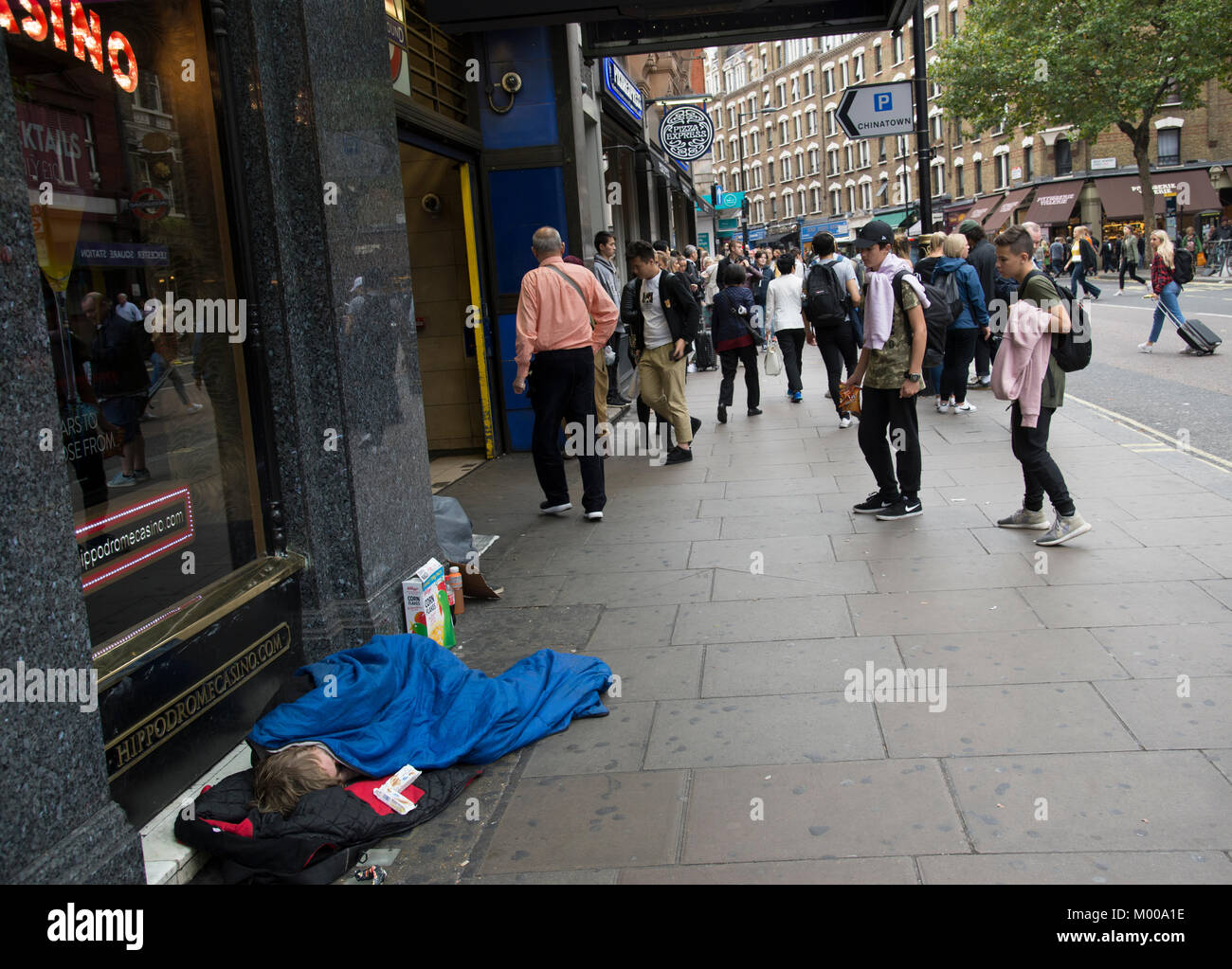 A homeless person sleeps on the pavement right outside the Leicester Square tube station on Charing Cross road in - Stock Image