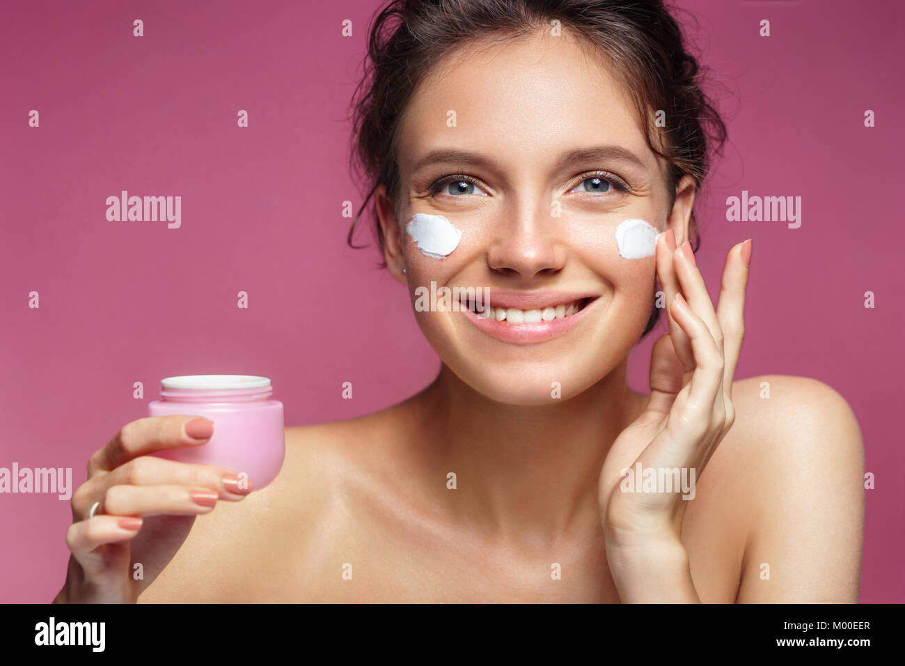 Woman applying wrinkle cream or anti-aging skin care cream. Photo of smiling woman with healthy skin on pink background. - Stock Image