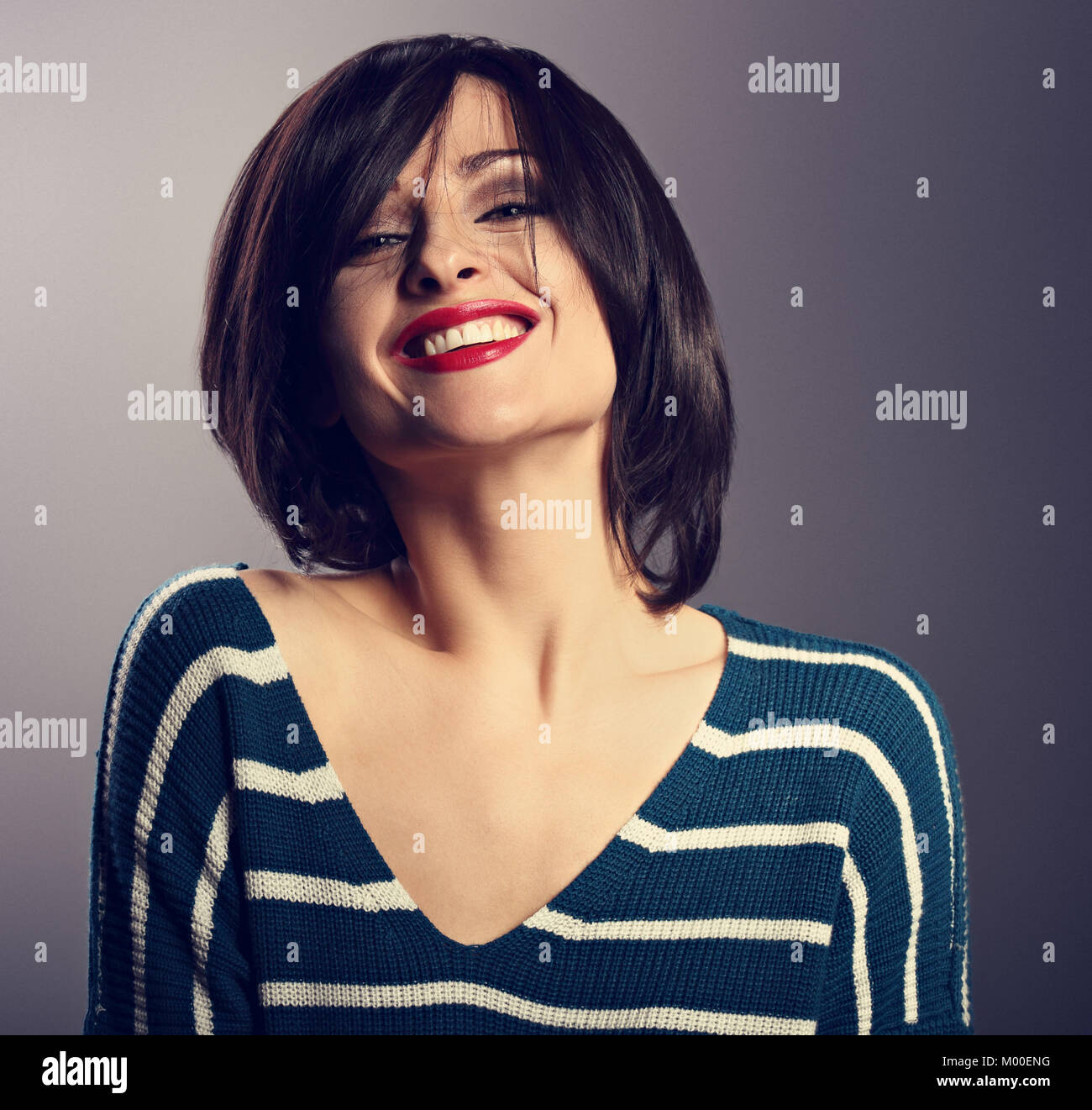 Happy loudly laughing with wide smile young woman with short hair in fashion sweater. portrait on grey background. - Stock Image