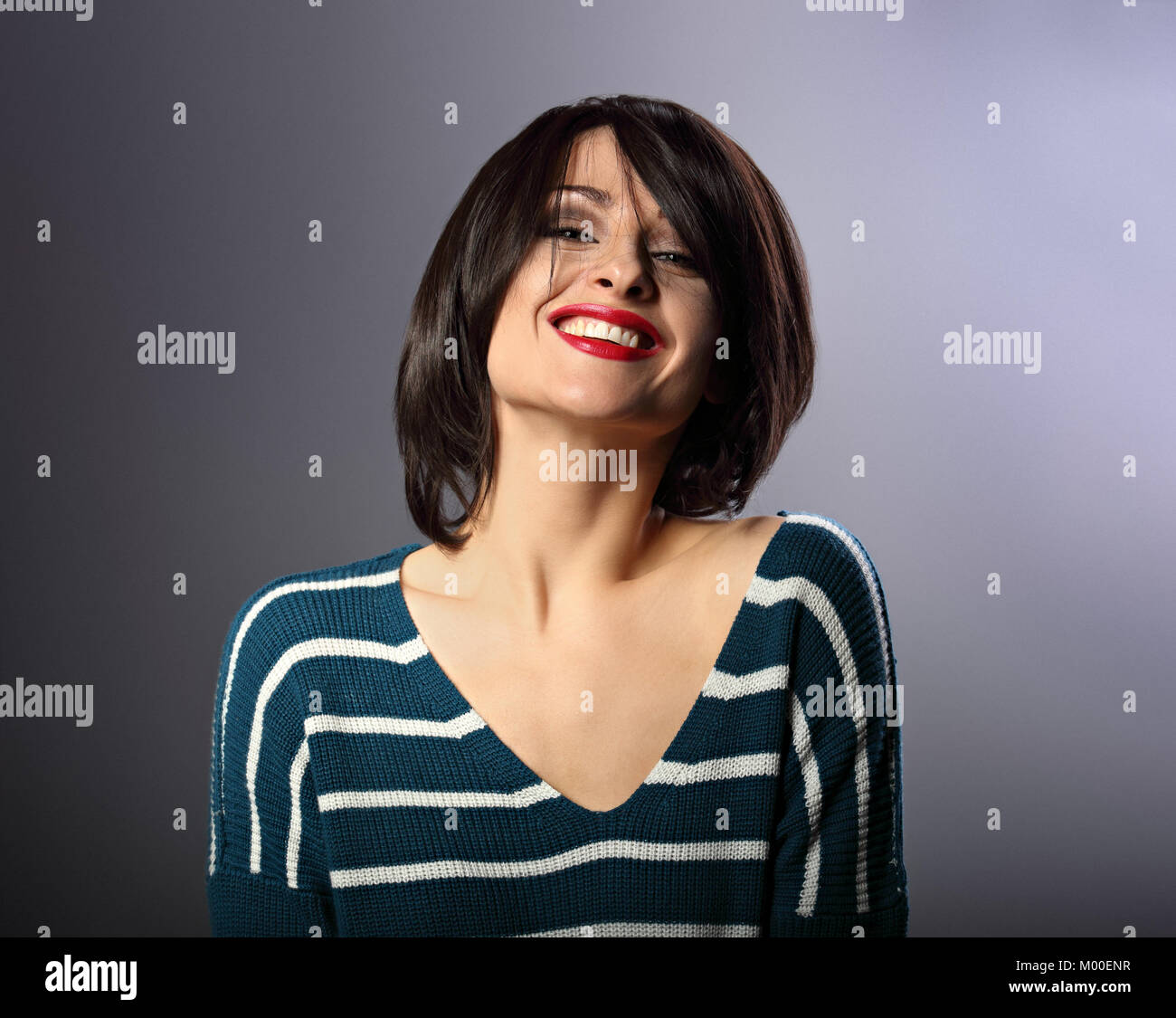 Happy loudly laughing with wide smile young woman with short hair in fashion sweater. portrait on grey background - Stock Image
