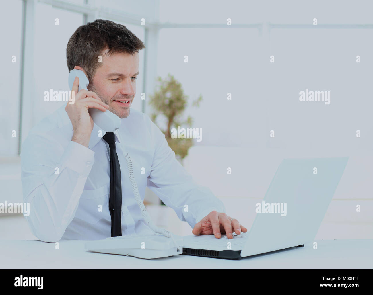 businessman working at the computer and talking on the phone. - Stock Image
