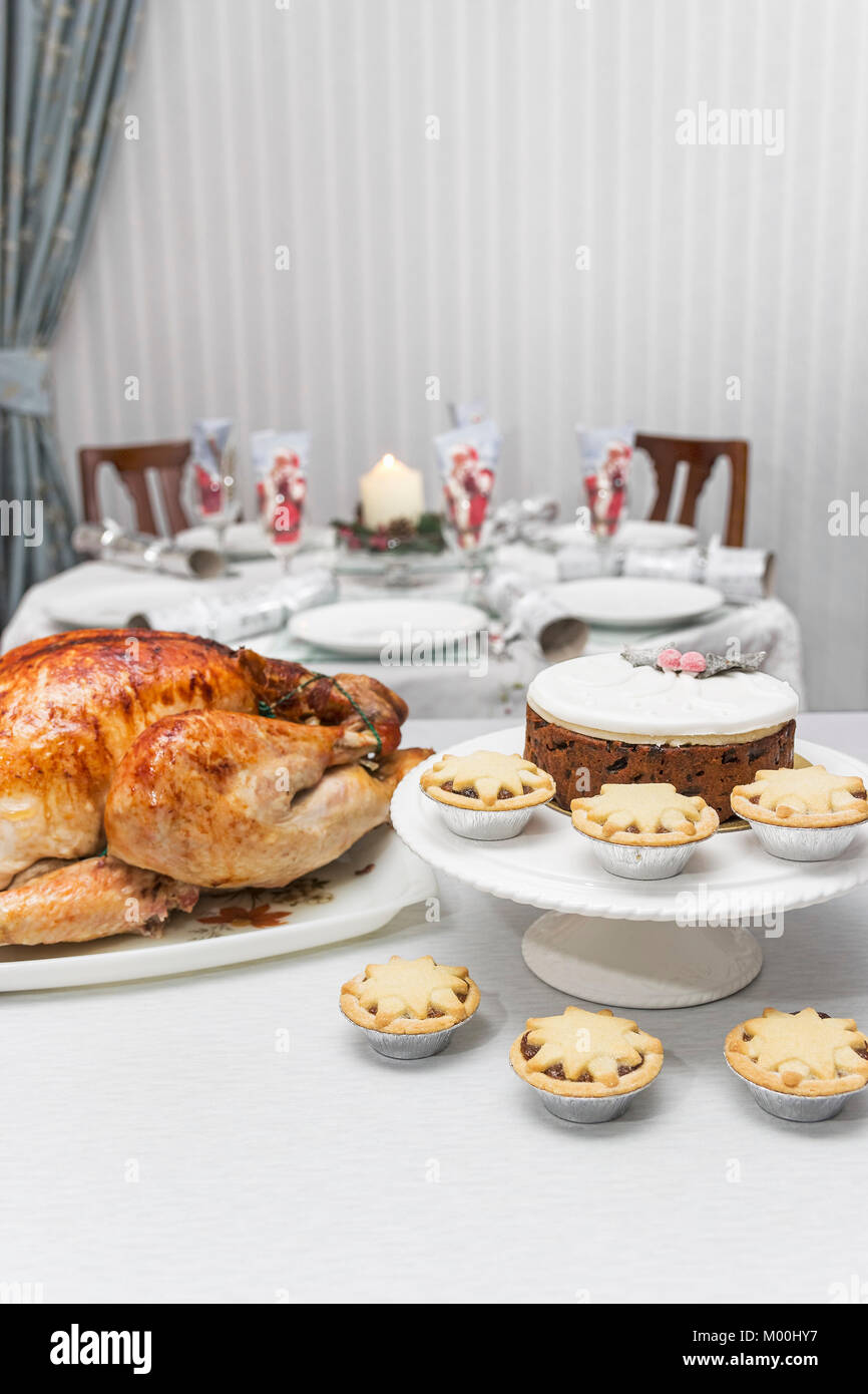 Seasonal food of roast turkey, mince pies and Christmas cake with a set dining table in the background. - Stock Image