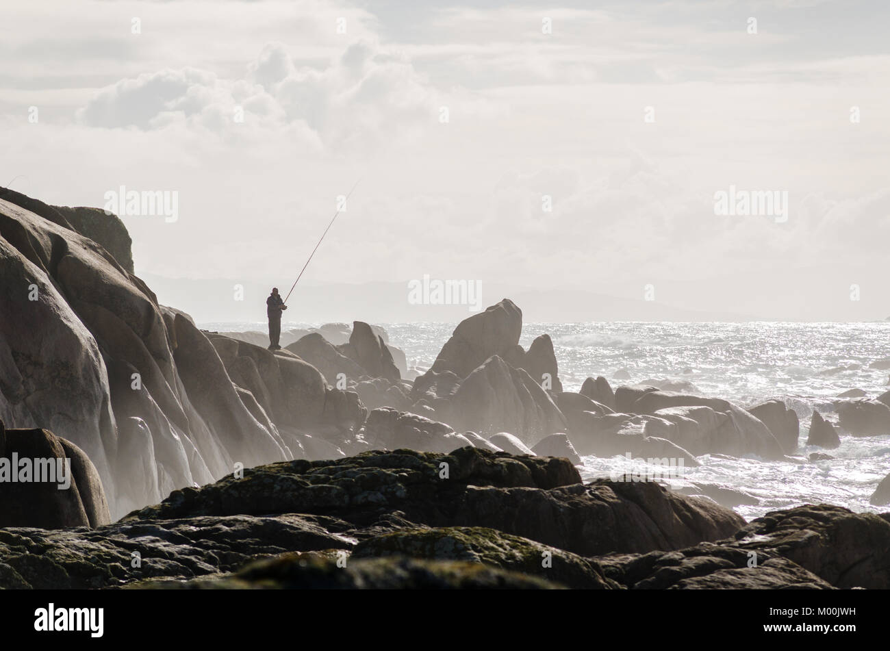 Fisherman fishing on coastline rocks. Brown tones - Stock Image