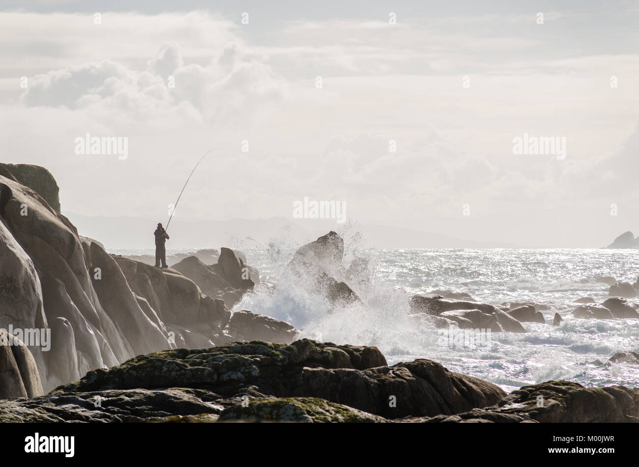 Fisherman fishing on coastline rocks. Brown tones. Waves crashing - Stock Image