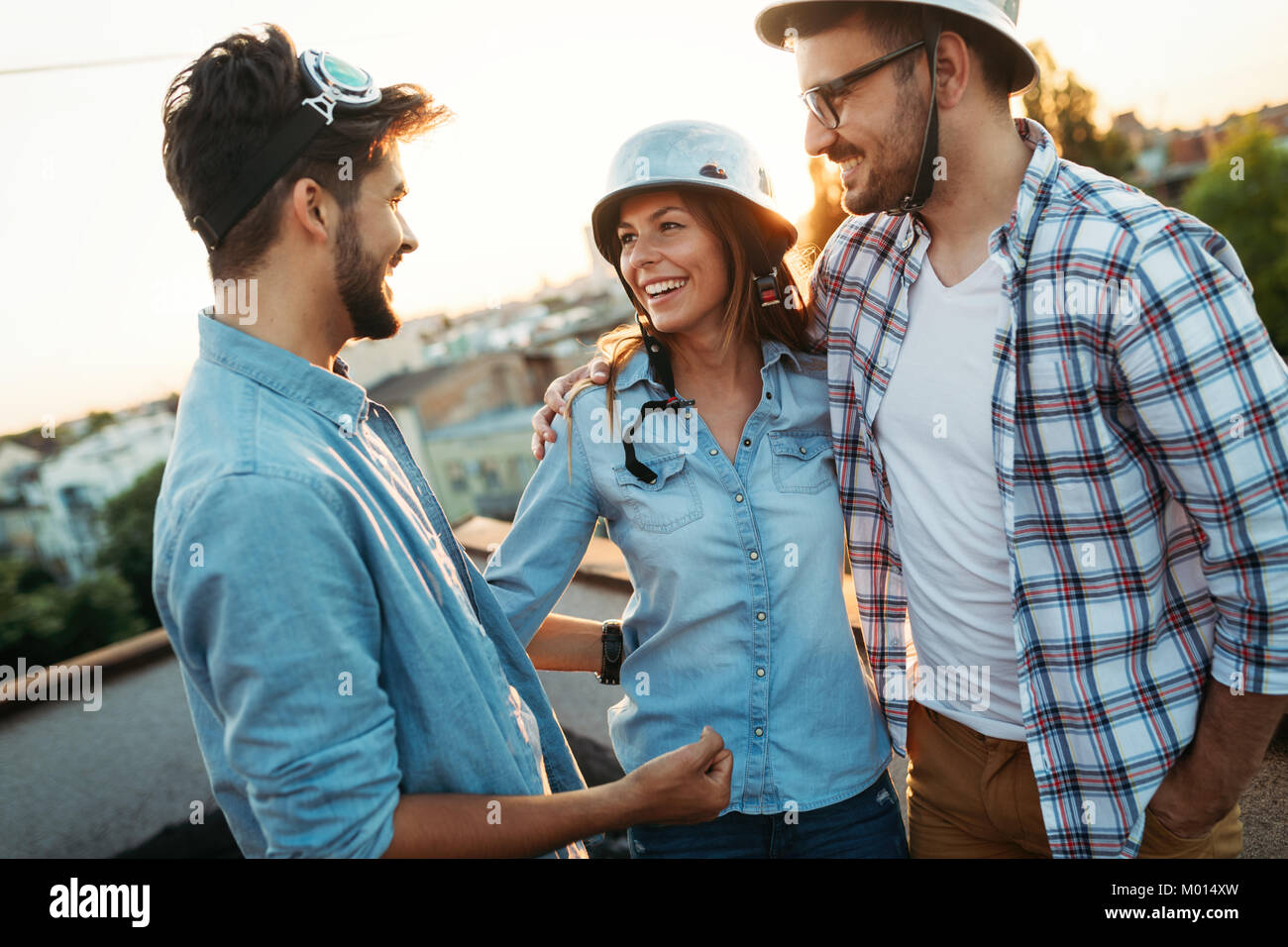Happy friends laughing and smiling outdoors - Stock Image