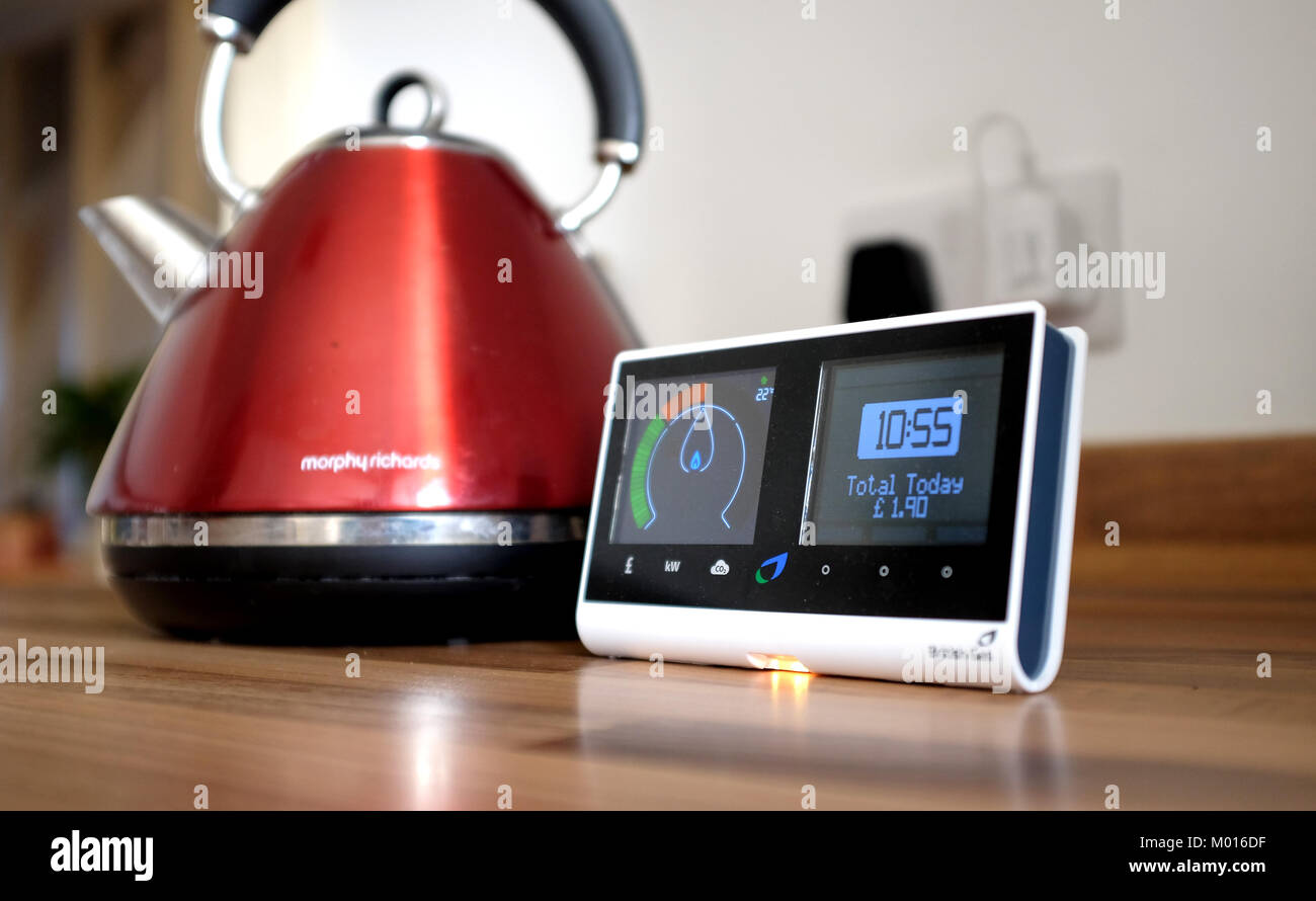 British Gas Smart meter showing how much energy being used in household with boiling kettle in background - Stock Image