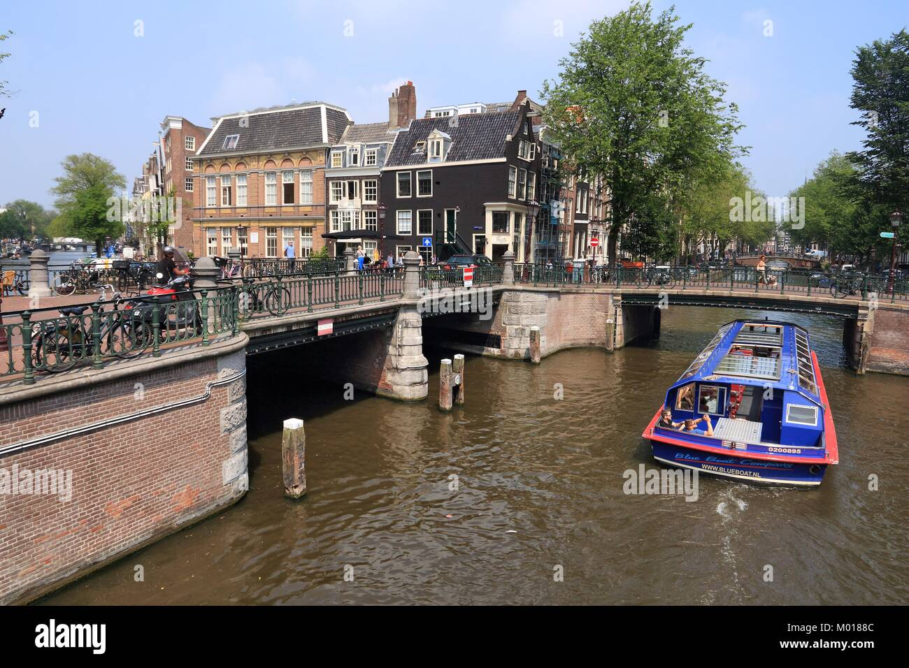AMSTERDAM, NETHERLANDS - JULY 7, 2017: People visit Leidsegracht and Prinsengracht canal crossing in Amsterdam, - Stock Image