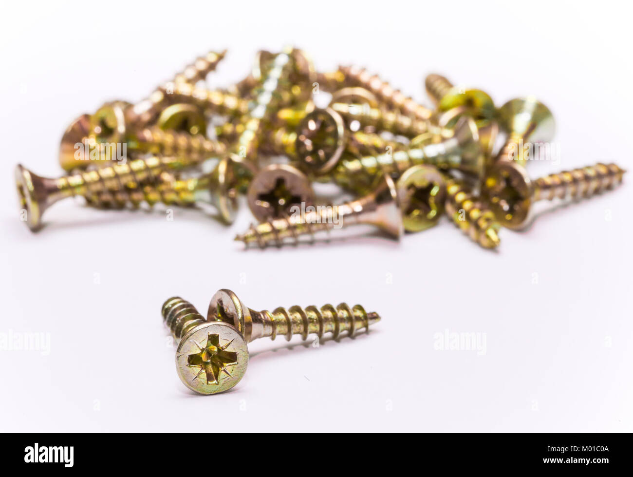 Bunch of yellow zinc coated philips flat head cross screws - fasteners on a white background - Stock Image