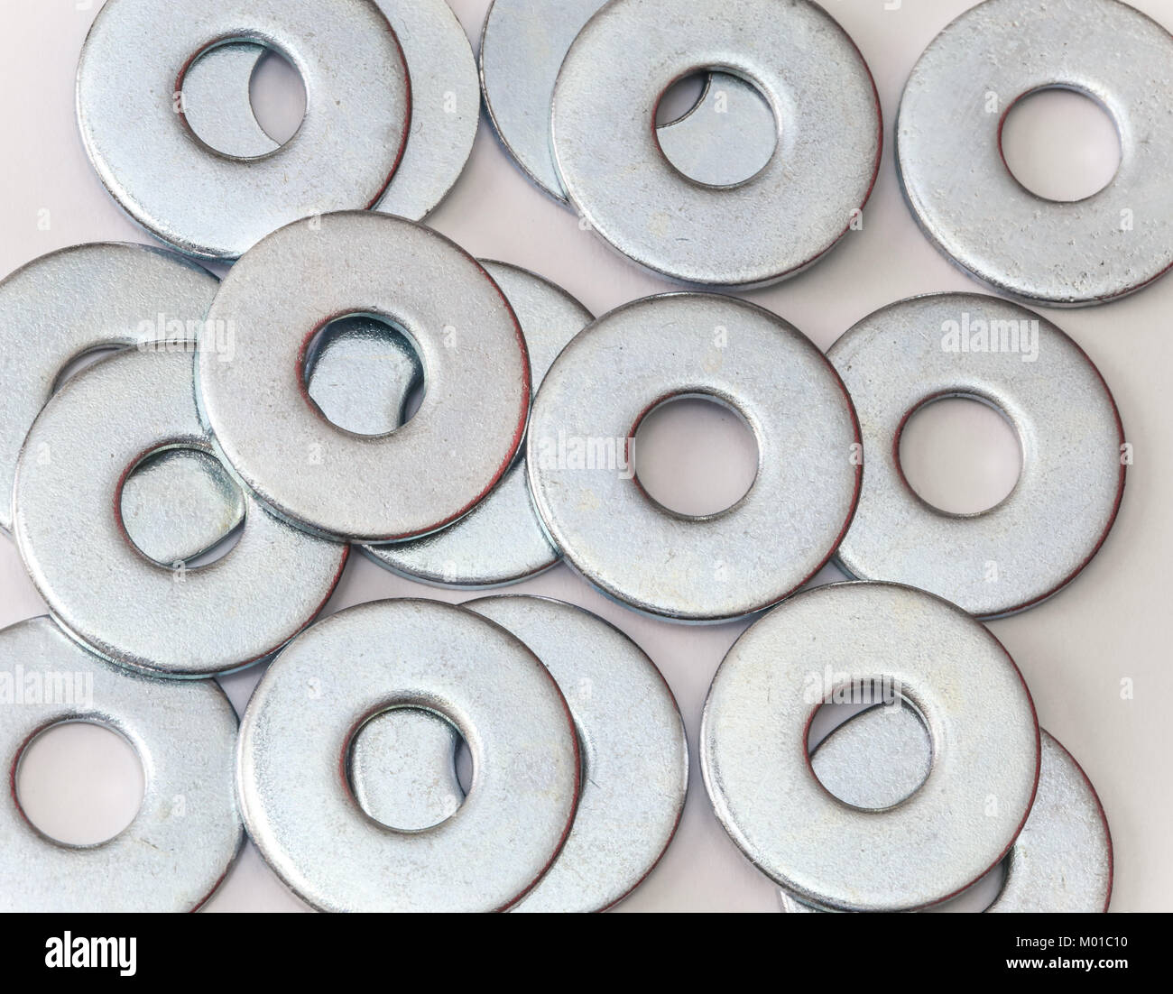 Pile of flat metal washers for screws and fasteners - Stock Image