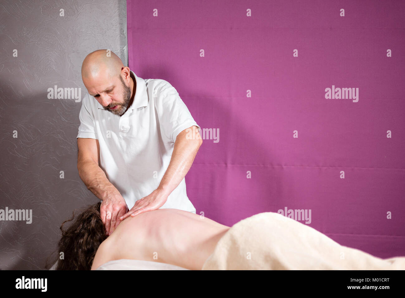 Masseur hands doing spine and back massage, neck and hand. Relaxed patient enjoys. Man hands massaging female. Spa - Stock Image