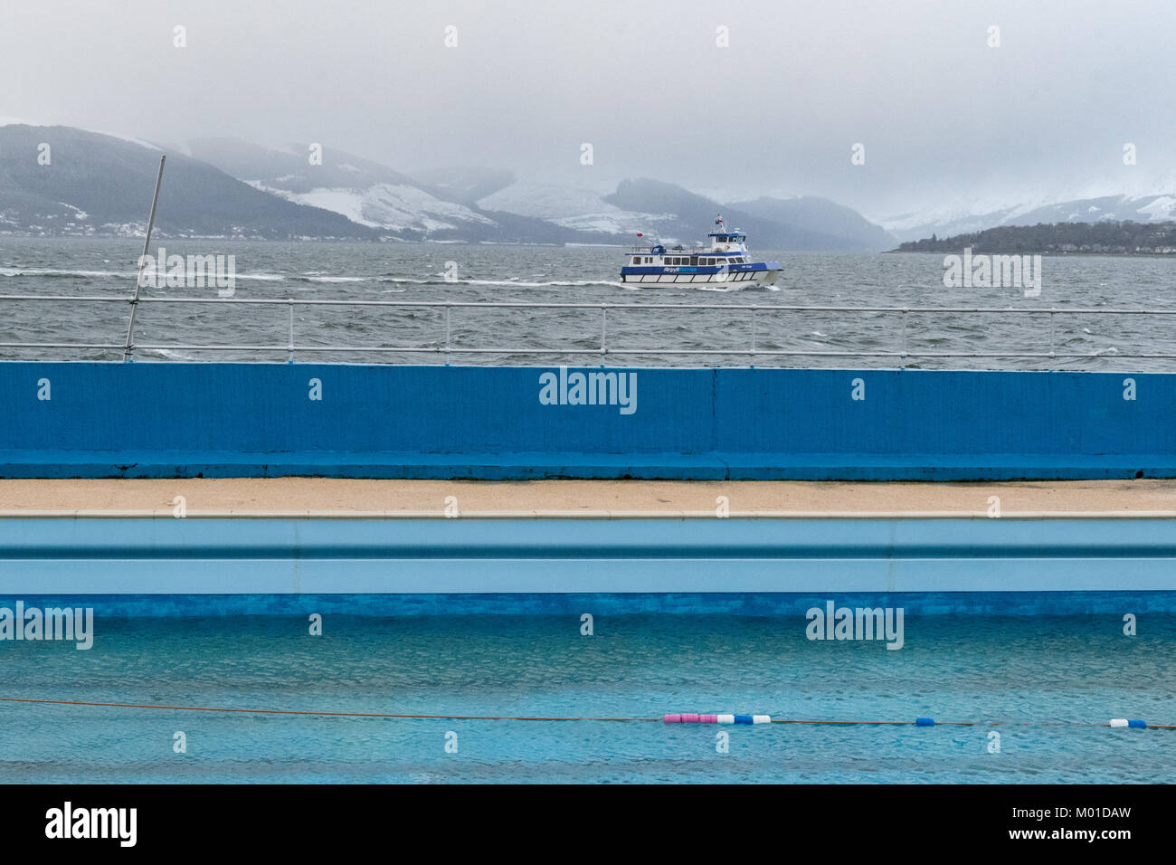 Gourock outdoor salt water heated swimming pool out of season, with ferry sailing across the Firth of Clyde behind, - Stock Image