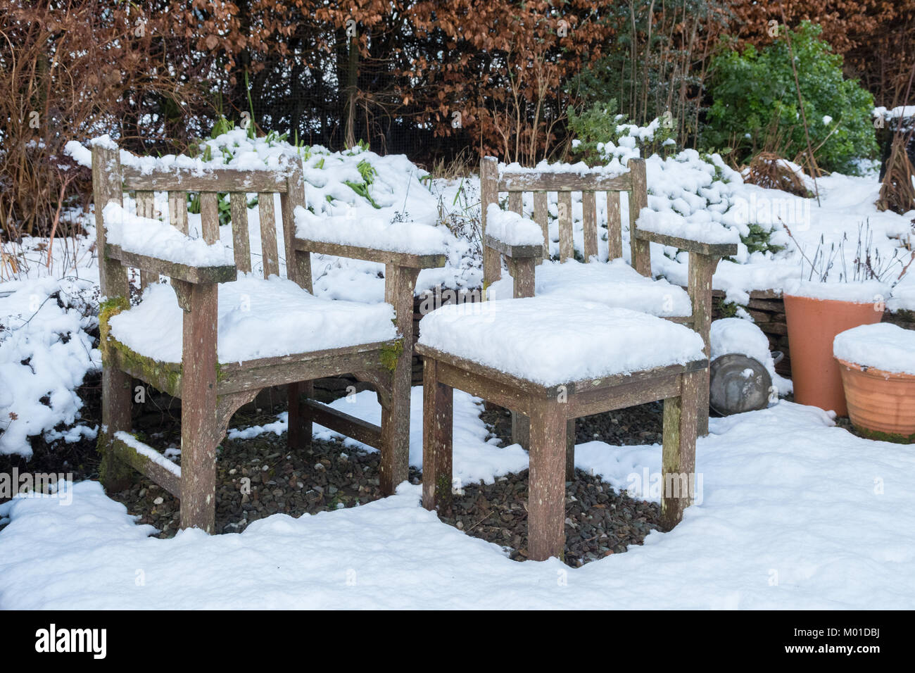 wooden garden furniture covered in snow - Stock Image