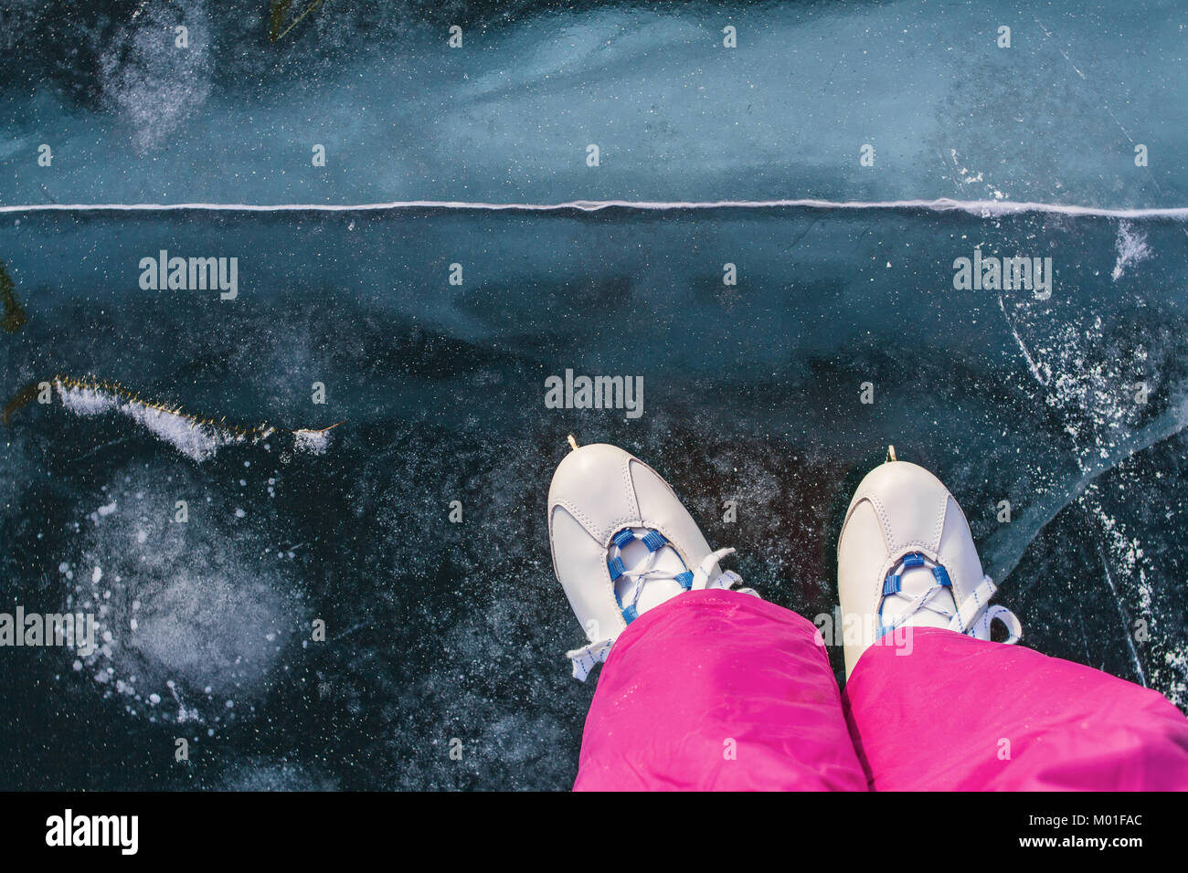 A girl skater in vintage skates and pink ski pants skates on the beautiful fairy blue clear ice of Lake Baikal with - Stock Image