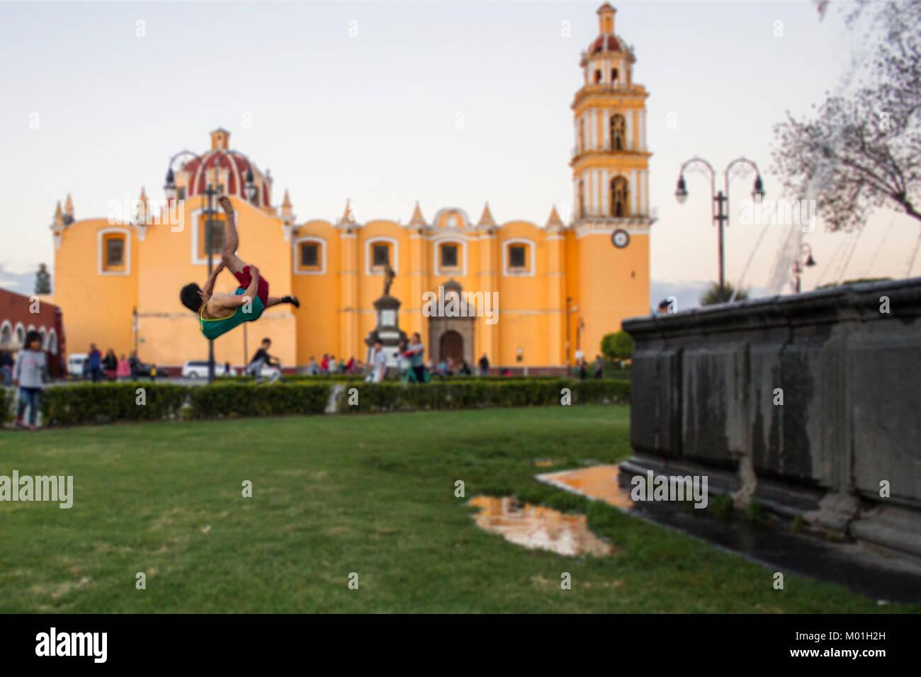 Cholula Mexico Church with parkour man doing backflip - Stock Image