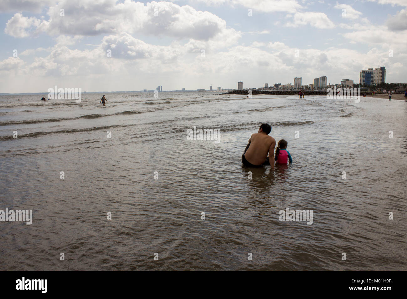 Man and girl in the water at the beach - Stock Image