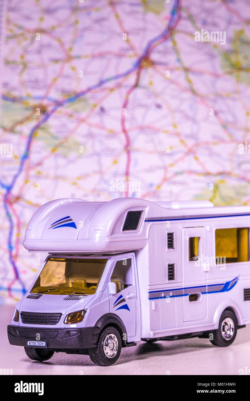Model motorhome / campervan with defocused map / atlas in the background. Concept of any aspect of camping / touring - Stock Image