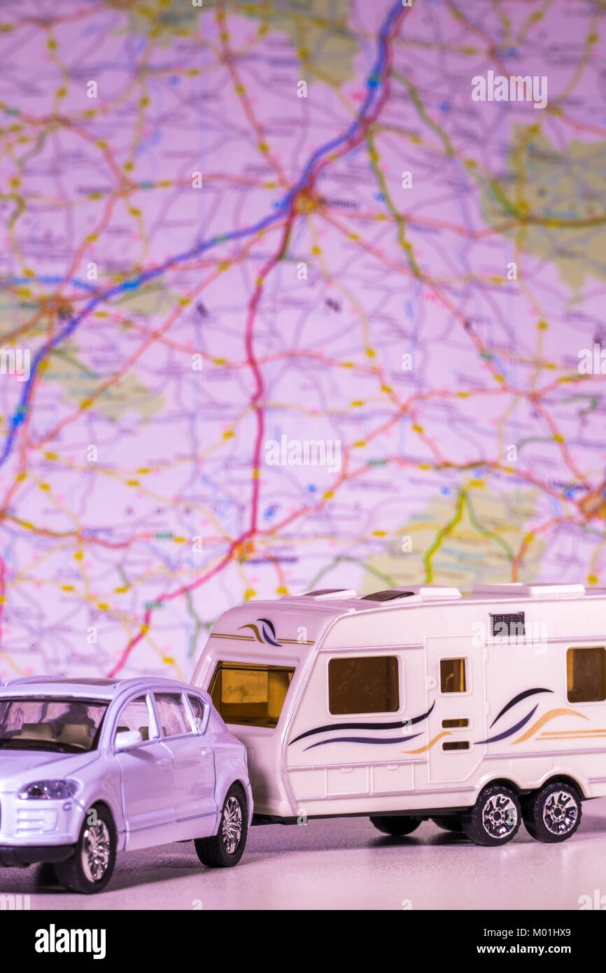 Model caravan and car with a defocused map / atlas in the background. Concept of any aspect of camping / touring / freedom of the open road, etc. Stock Photo