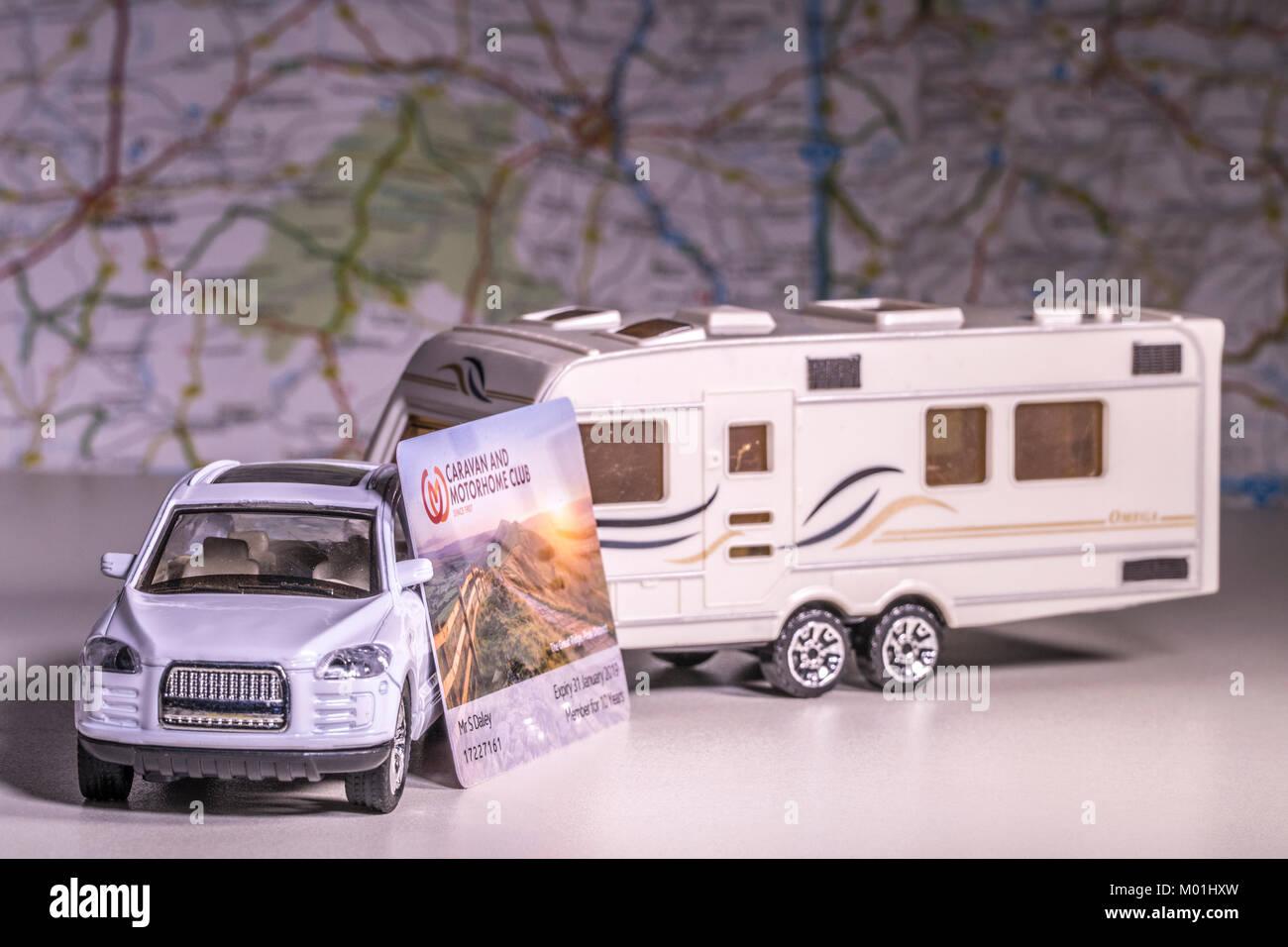 Model caravan and car with UK 'Caravan and Motorhome Club' membership card and defocused map / atlas. Concept of touring using a campsite network. Stock Photo