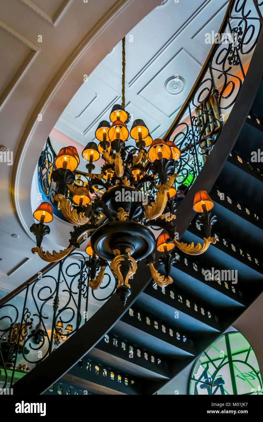 Architecture interior, candelabra and curved staircase viewed from below. Building interior detail, spiral staircase, - Stock Image