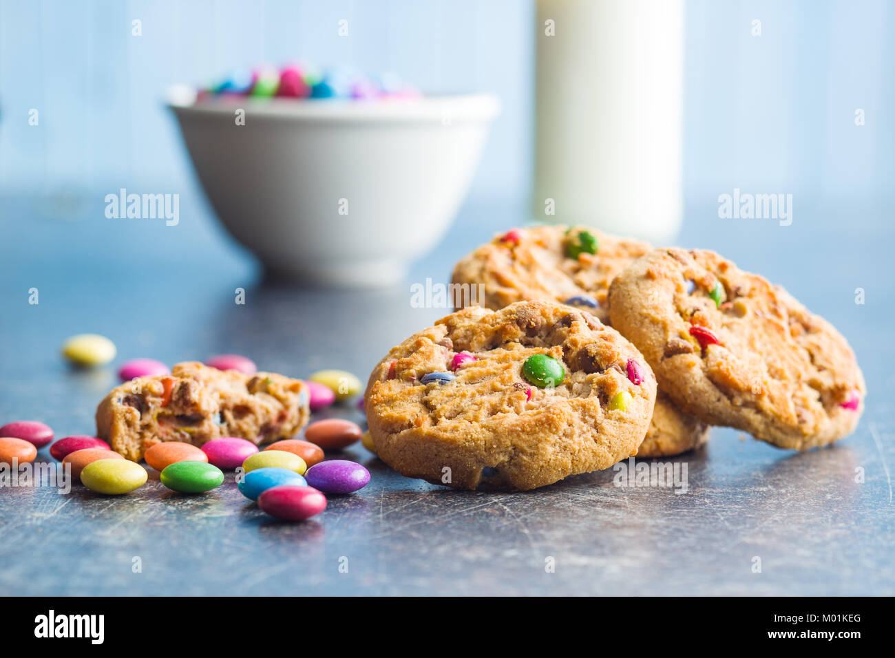 Sweet cookies with colorful candies on old kitchen table. - Stock Image