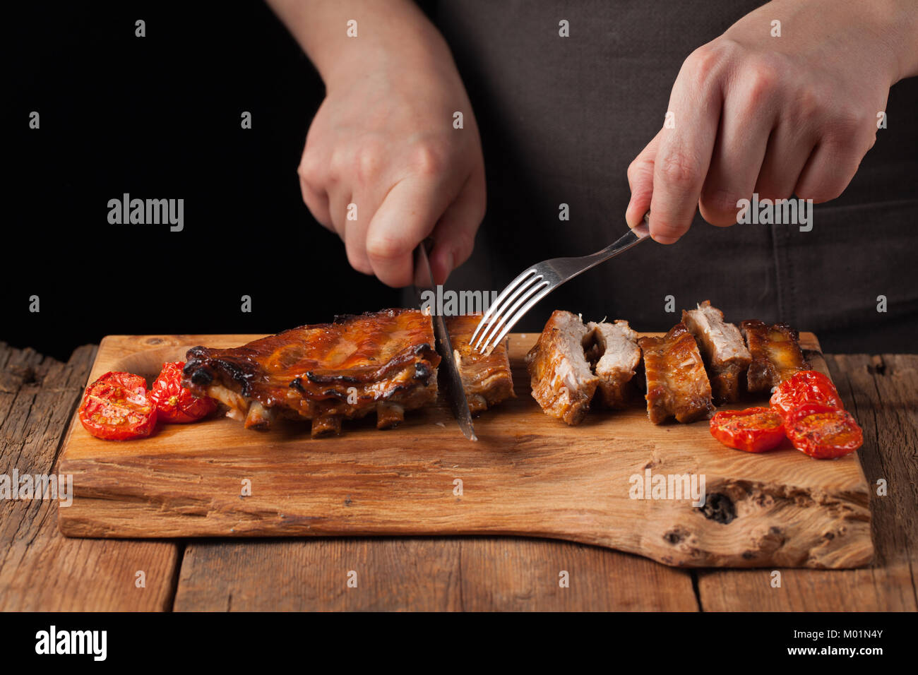 The chef cuts it with a sharp knife ready to eat pork ribs, lying on an old wooden table. A man prepares a snack - Stock Image