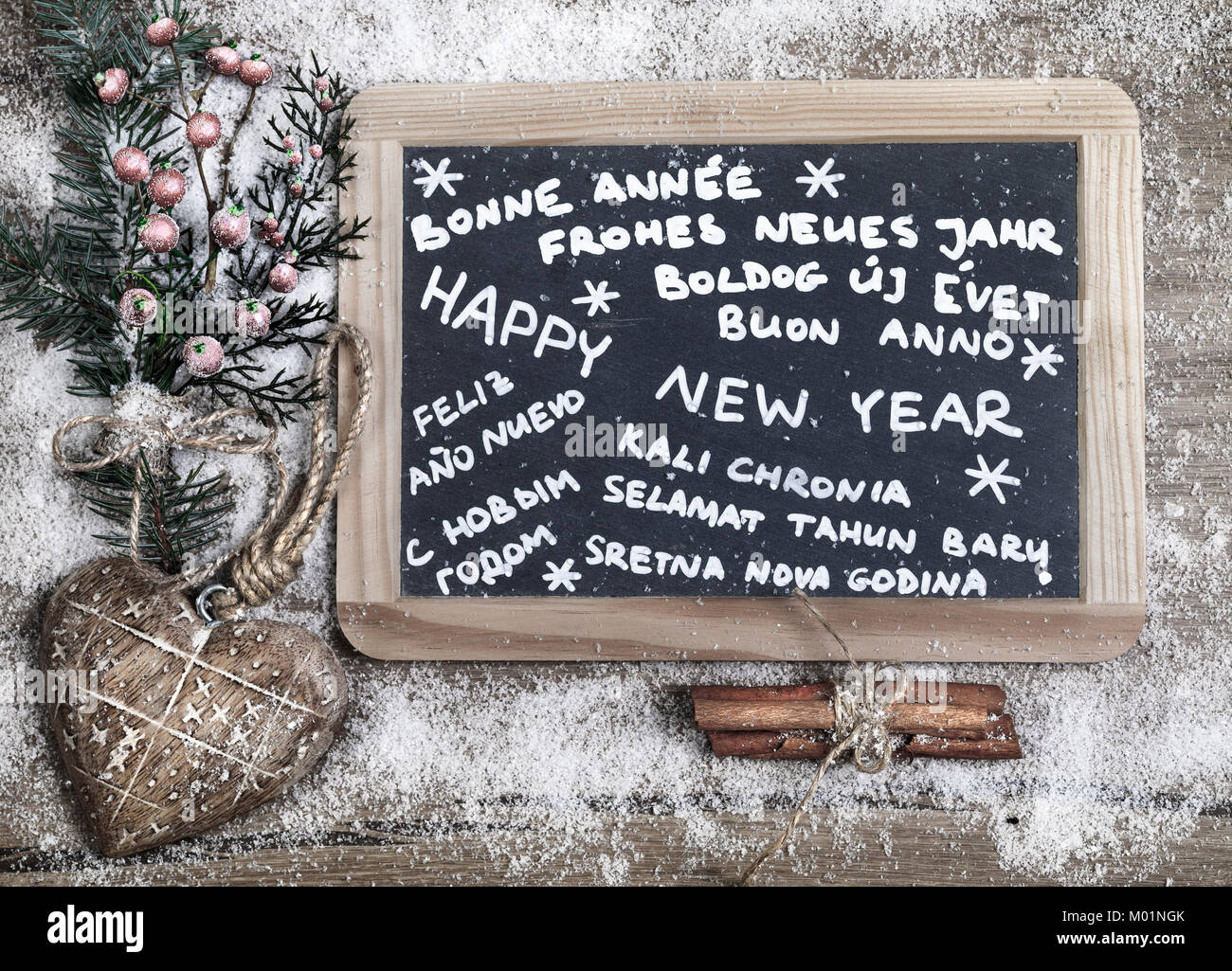 'Happy new year' in different languages written on a chalkboard with winter decorations - Stock Image