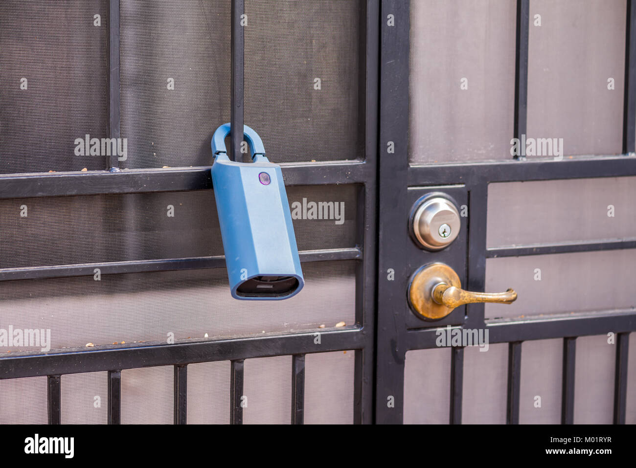 Real Estate lock box on a gate to a house. This way agents have access to a key and can show the house to clients. - Stock Image
