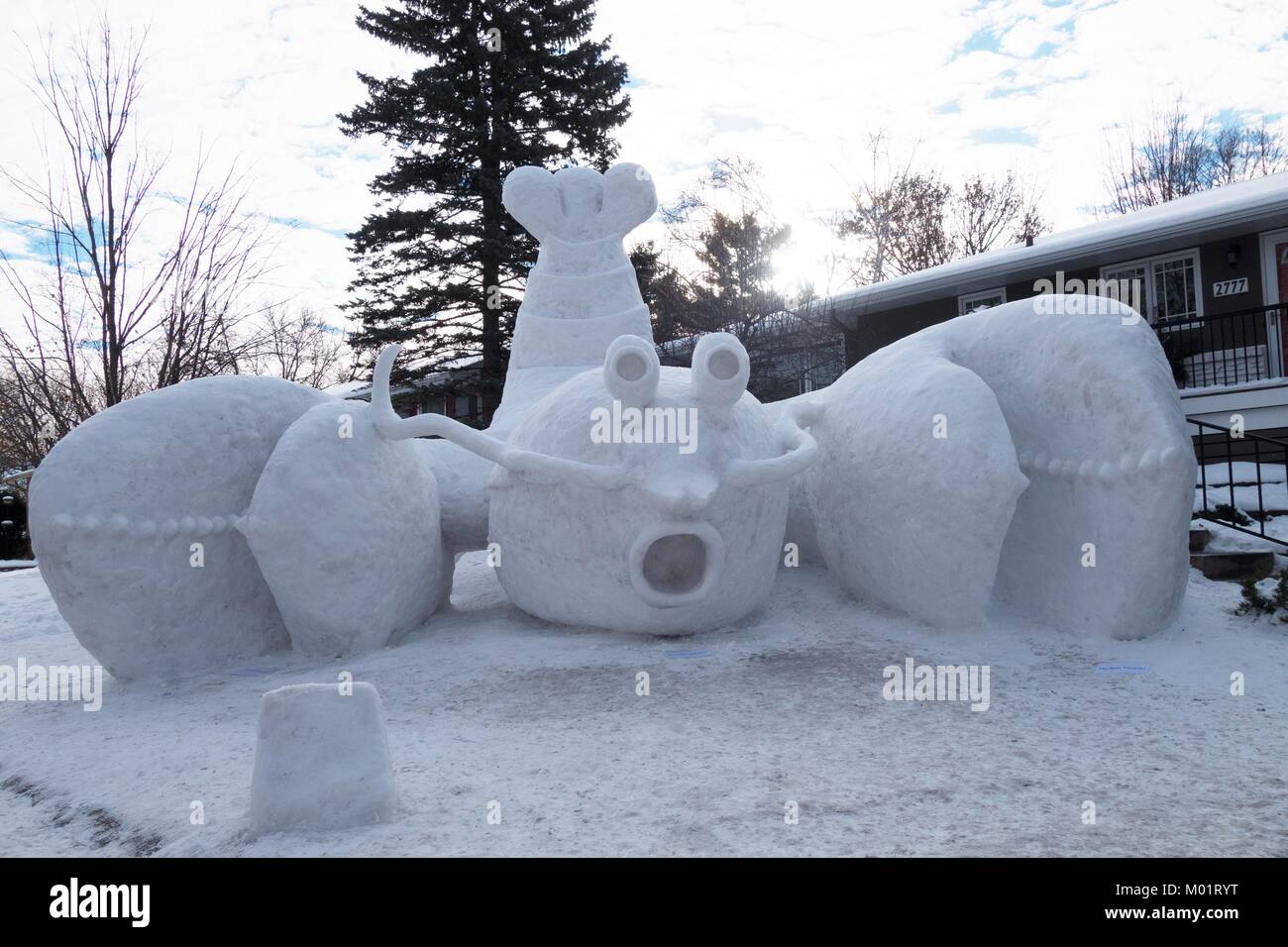 A giant lobster snow sculpture in the front yard of a home in New Brighton, Minnesota, USA, created by the Bartz - Stock Image