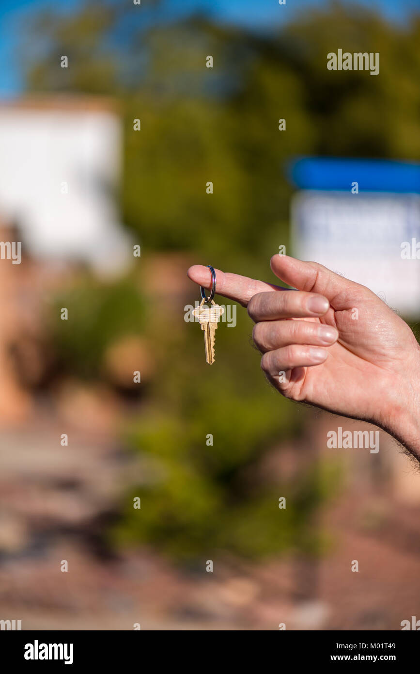 Handing over keys to a house after a successful home purchase; also indicating success. - Stock Image