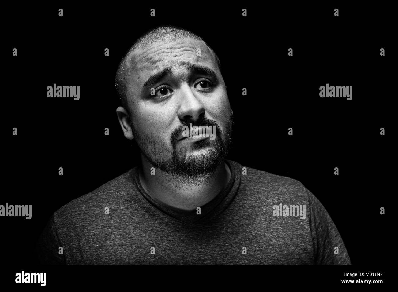 A high contrast black and white emotional and sad portrait of a hispanic man. - Stock Image